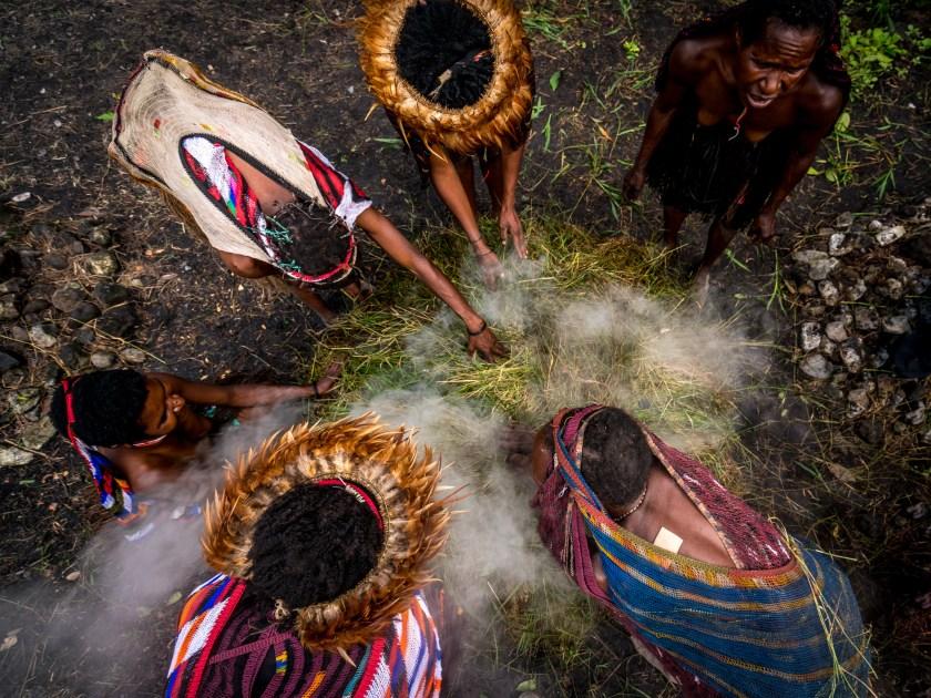 Dunia modern belum sampai pada suku yang terisolasi ... Dani tribeswomen menggunakan oven tradisional untuk memasak makanan