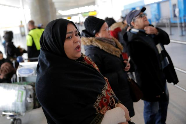 A Muslim woman waits for her family to arrive at the airport in New York