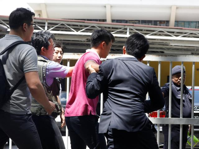 Journalists try to talk to a North Korean official (in pink) at the morgue at Kuala Lumpur General Hospital