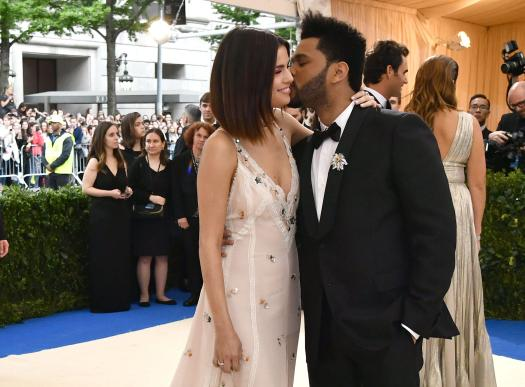 The Weeknd gave Selena a cute kiss as he wrapped his hands around her
