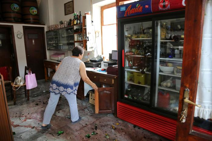 A woman clears her shop after the magnitude 6.2 quake