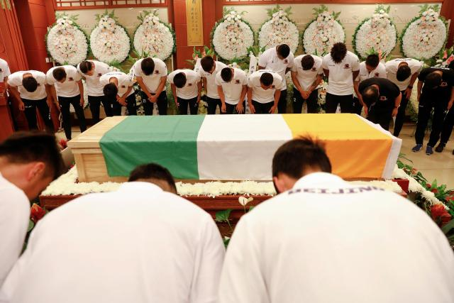 Beijing Enterprises players bow their heads in tribute to former team-mate Cheick Tiote