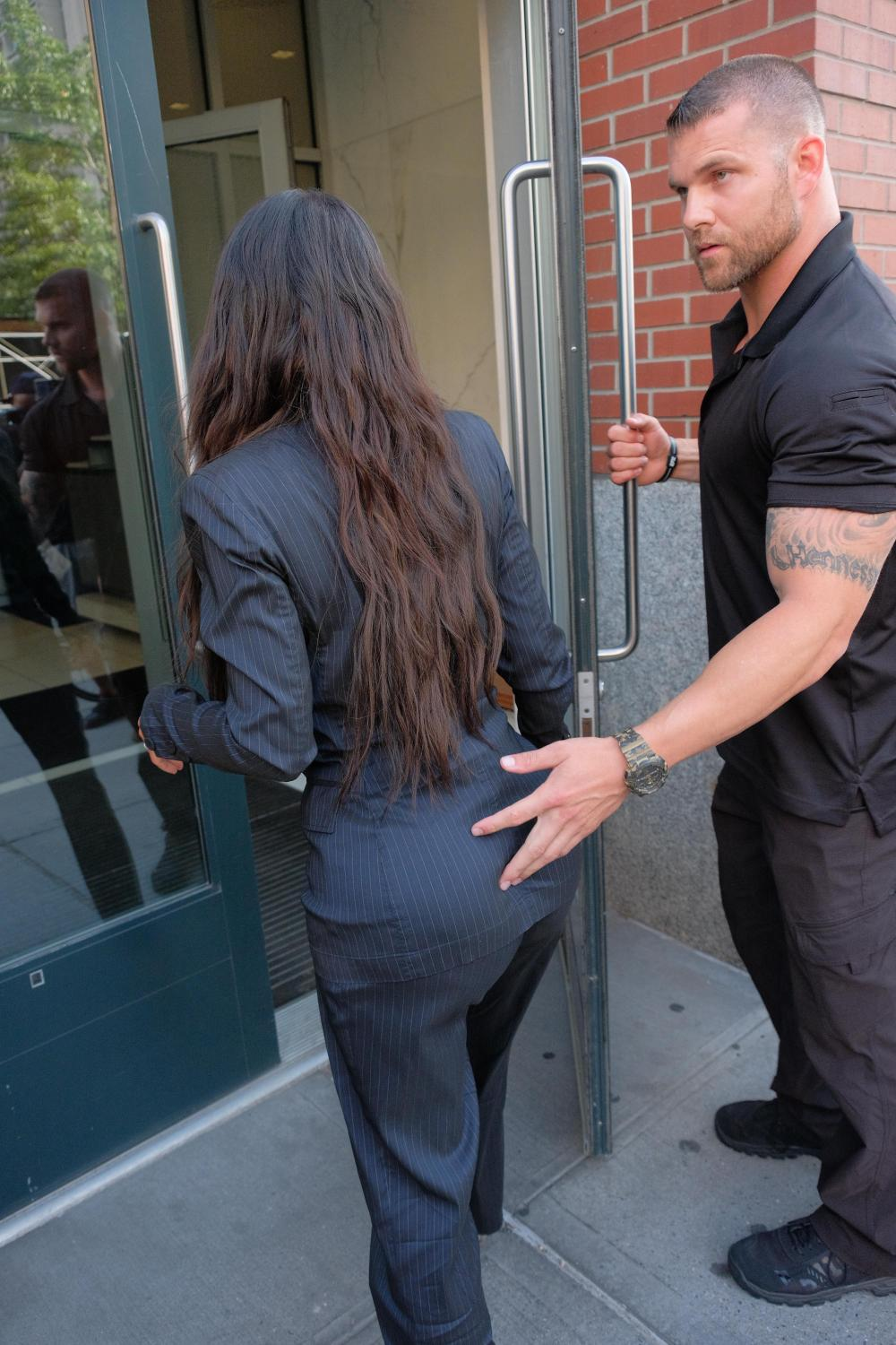 Kim Kardashian's bodyguard put his hand on her bum as he escorted her into her hotel yesterday