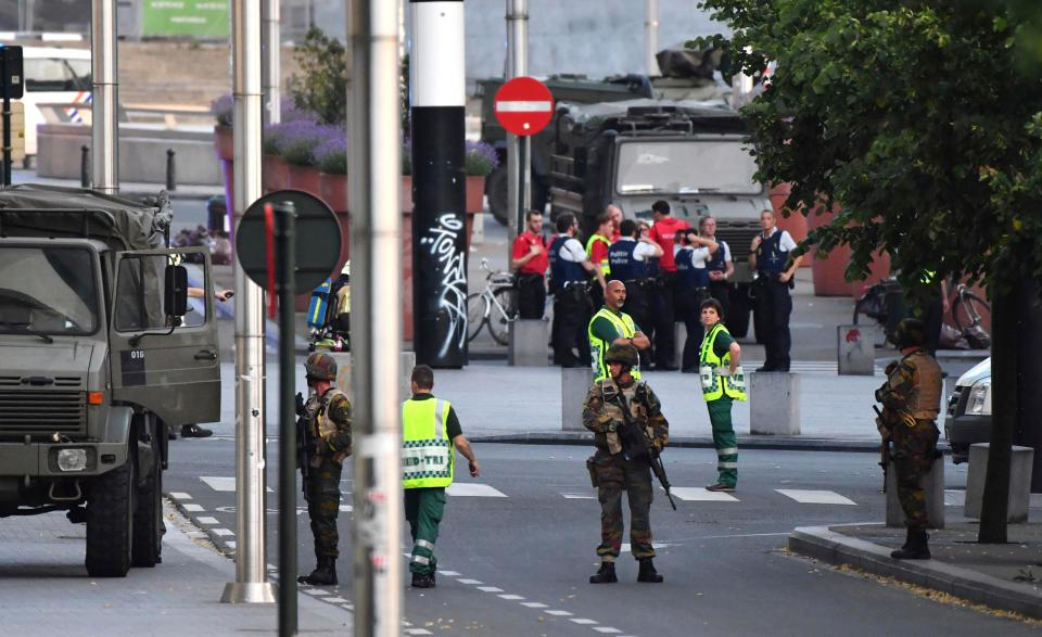 Police officials and soldiers stand alert in a cordoned off area outside Gare Centrale in Brussels
