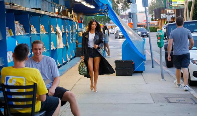 Kim Kardashian heads towards the restaurant as lads ogle her