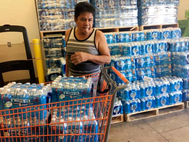 One worried local fills his trolley to the brim with bottled water