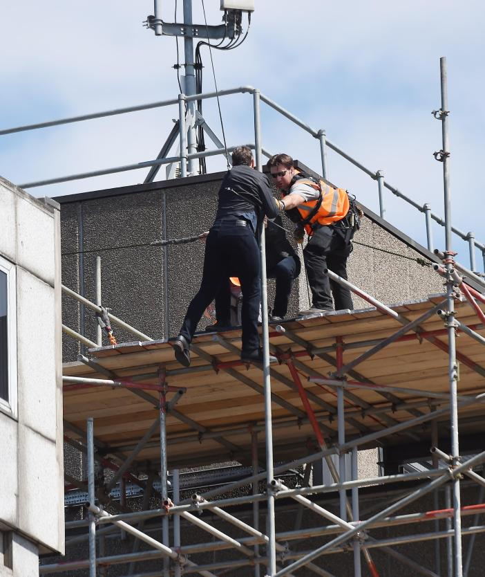 Crew were seen helping the mega-star back onto the scaffolding