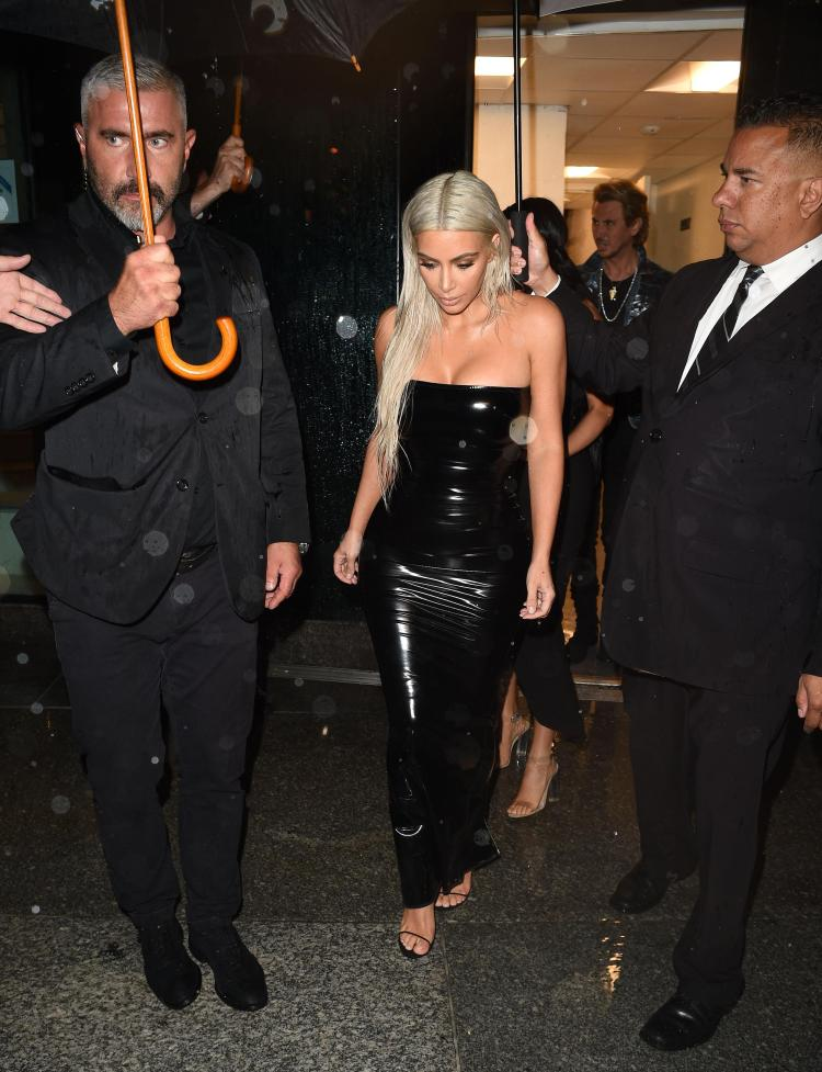 Kim strolled out of the show with assistants on hand to help protect her against the rain
