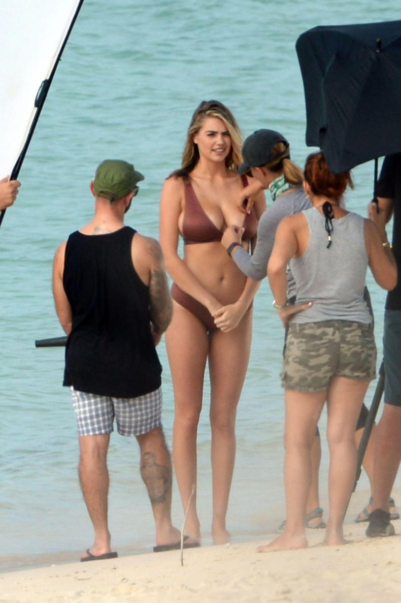 A member of the crew adjusted the beauty's bikini top for her