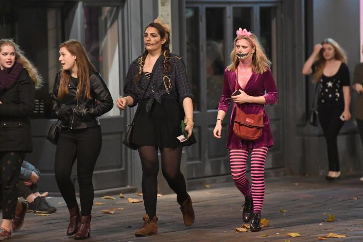 A Cheshire cat walks next to others donned in black