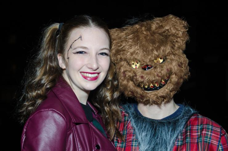 A heavily scarred woman poses with a terrifying bear with blood-soaked teeth