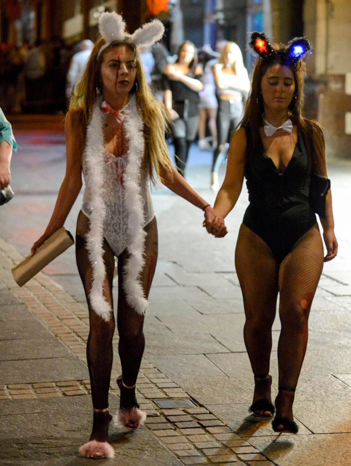 Women dressed as fluffy animals, with glowing ears, hold hands as they join Halloween parties in Newcastle