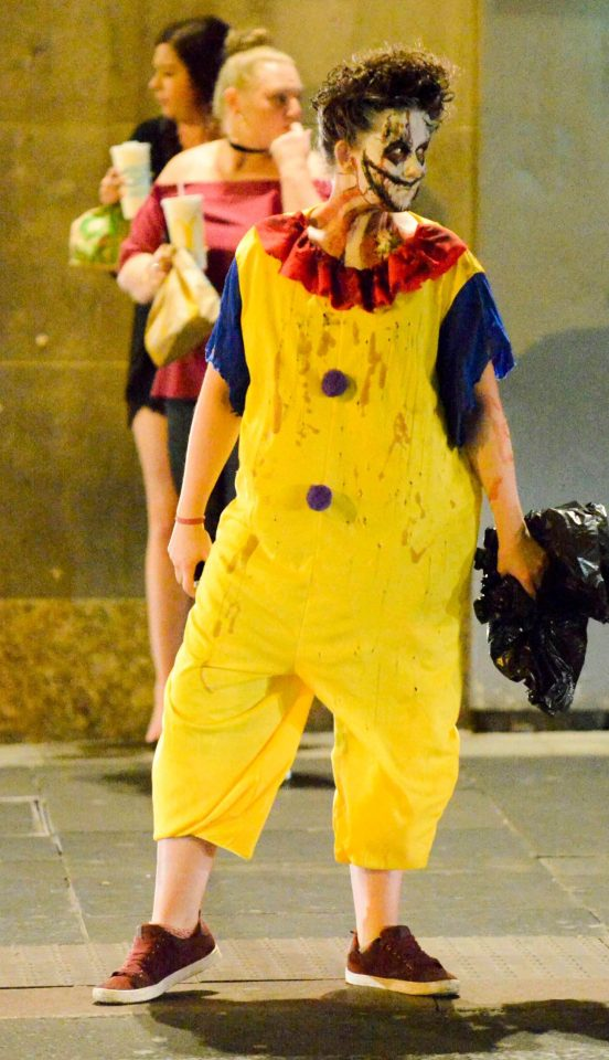 A scream-worthy clown looks to her left as she poses on the street