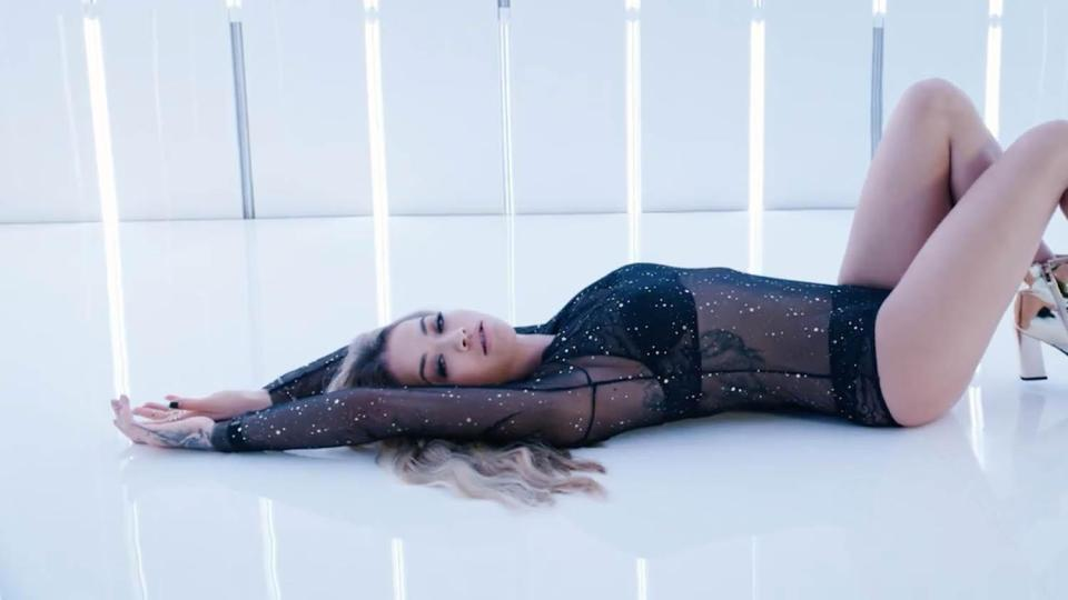 Another shot shows the singer lying down wearing a sheer body suit