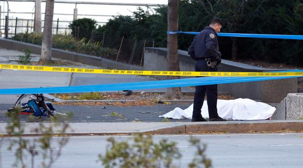 A NYPD police officer stands over a body covered by a sheet at the horrific scene on Tuesday