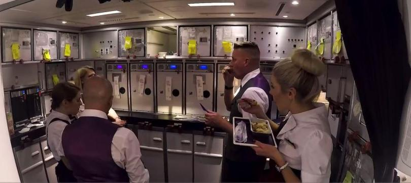 The busy crew are so rushed that they eat on their feet in the galley during a quick break