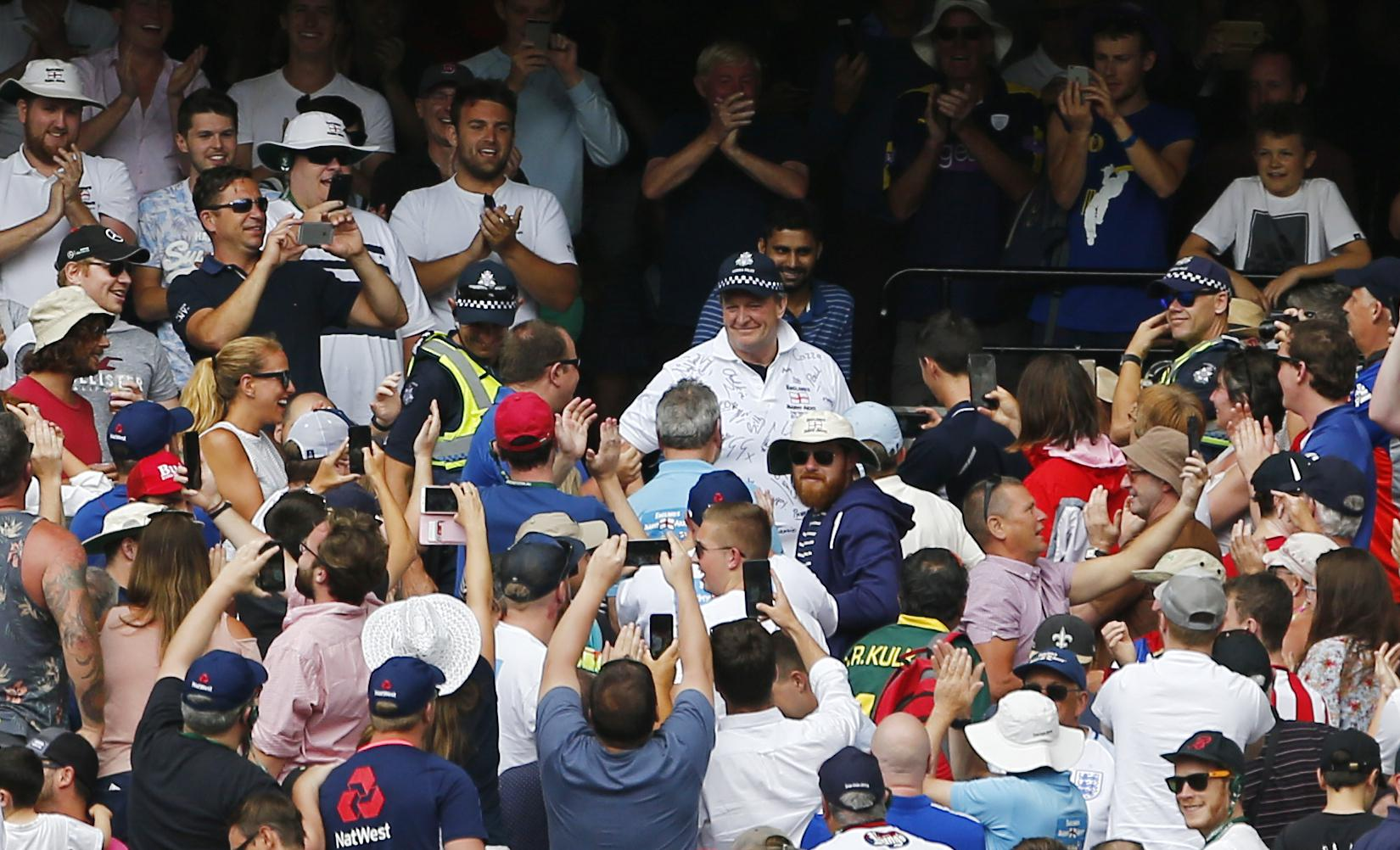 A police officer wears a Barmy Army shirt he was presented with by England fans