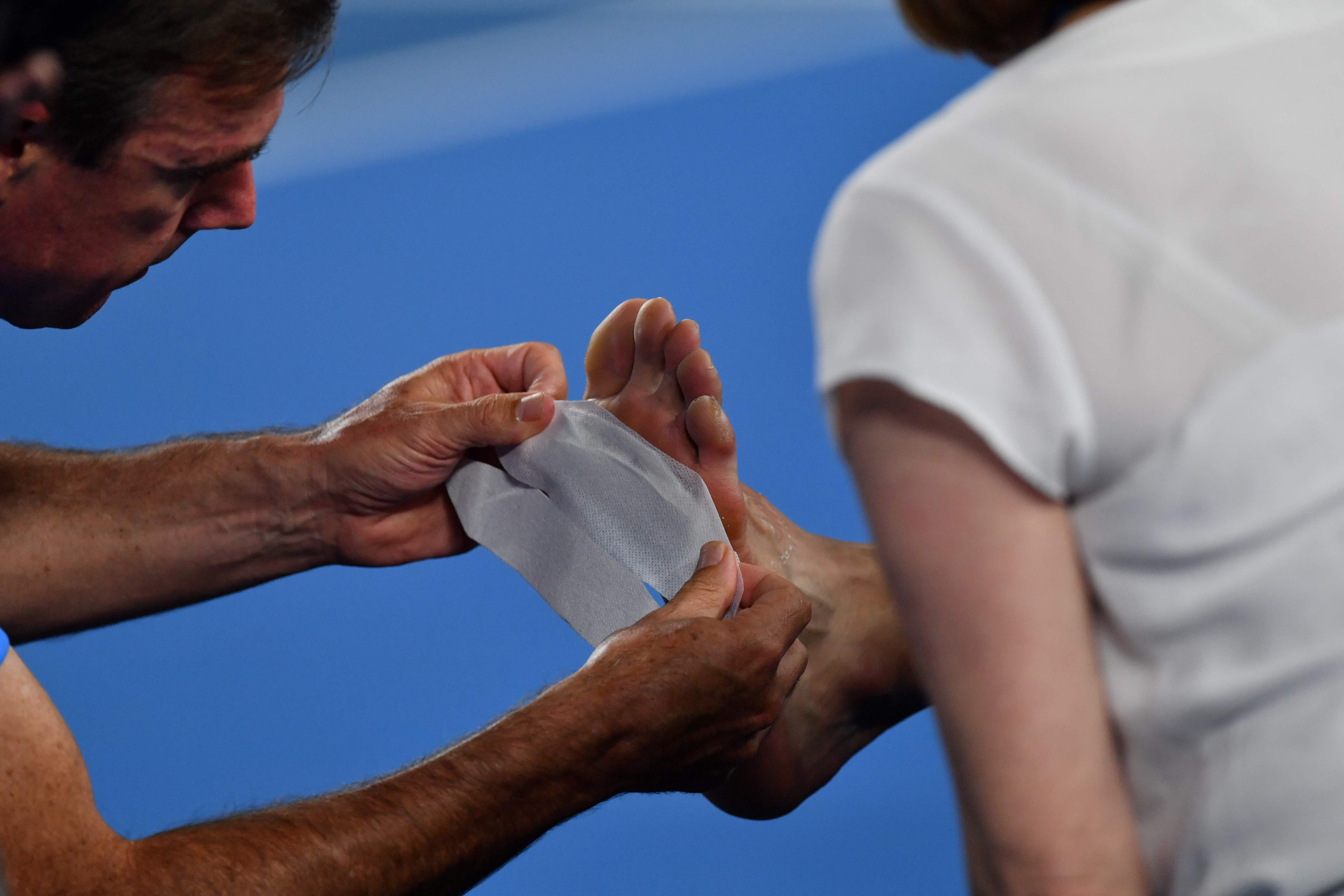 Medical team take a look at Chung Hyeon's foot during Roger Federer clash