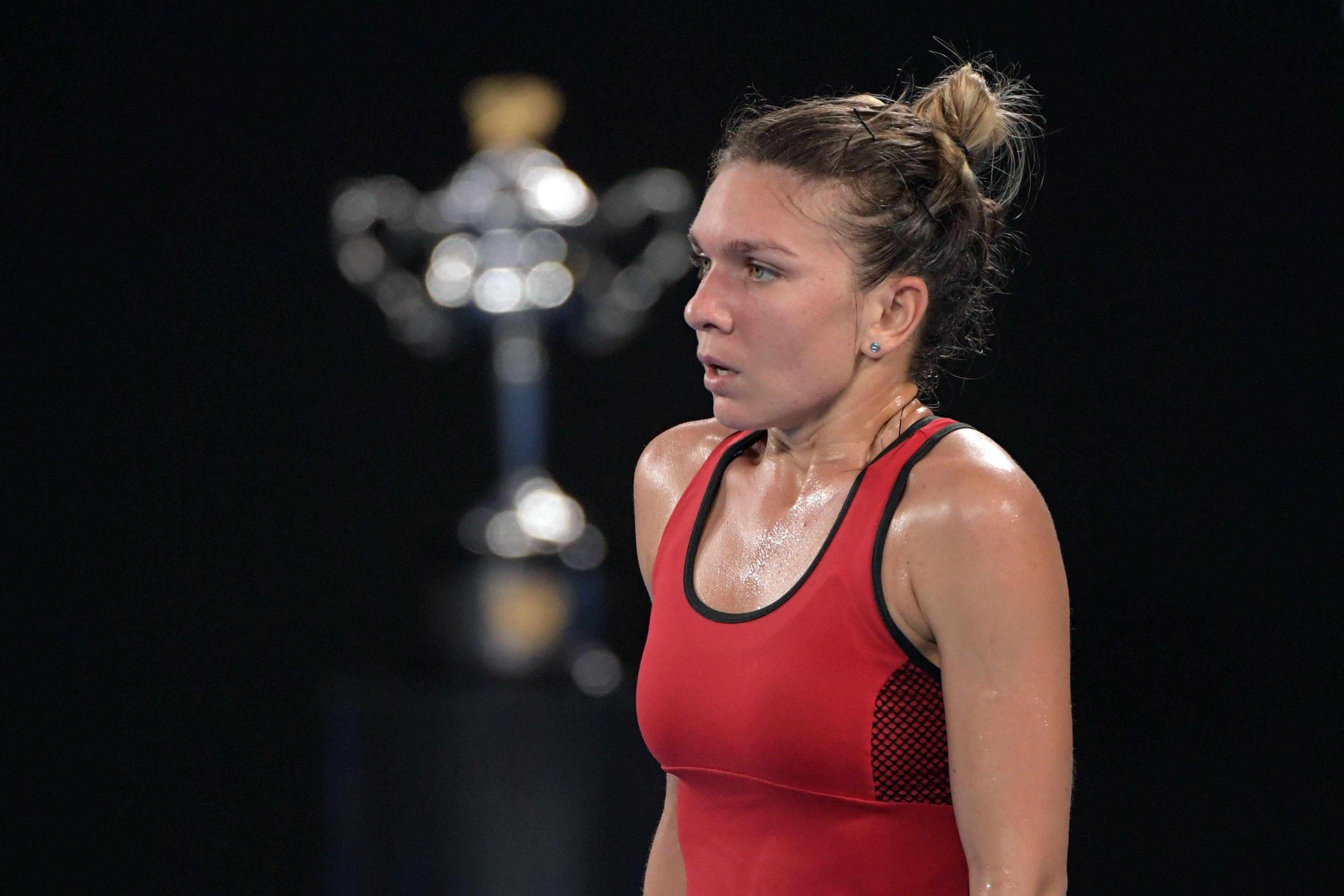 Halep stands in front of the Australian Open trophy