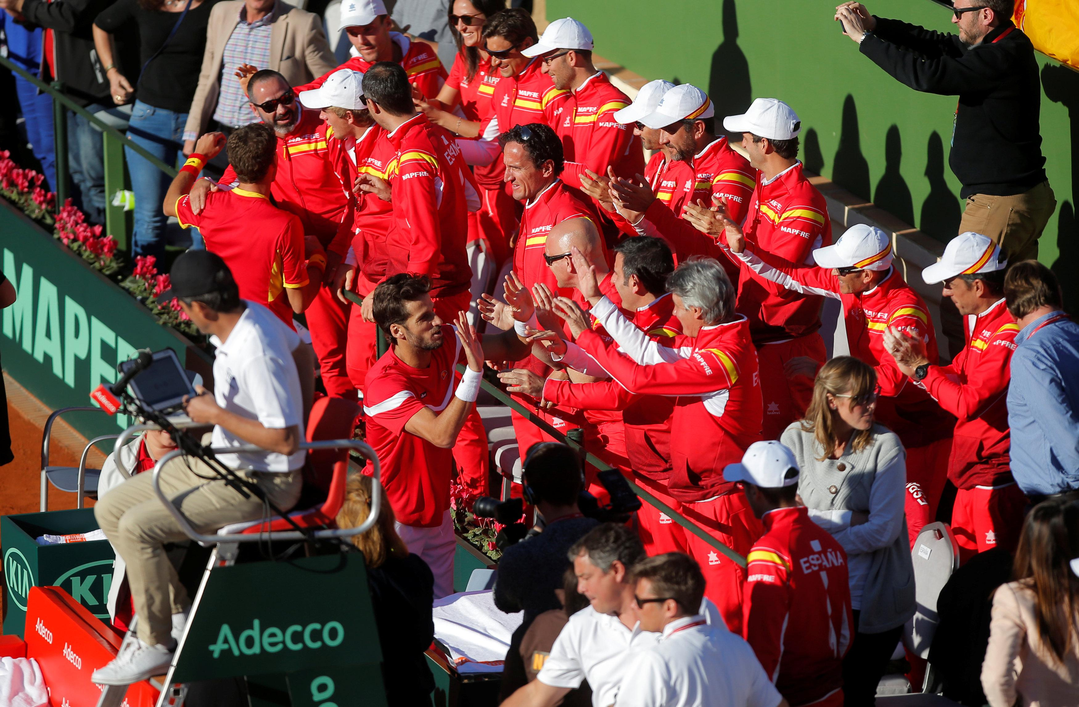 Pablo Carreno Busta and Feliciano Lopez celebrate with team mates after winning their doubles match.