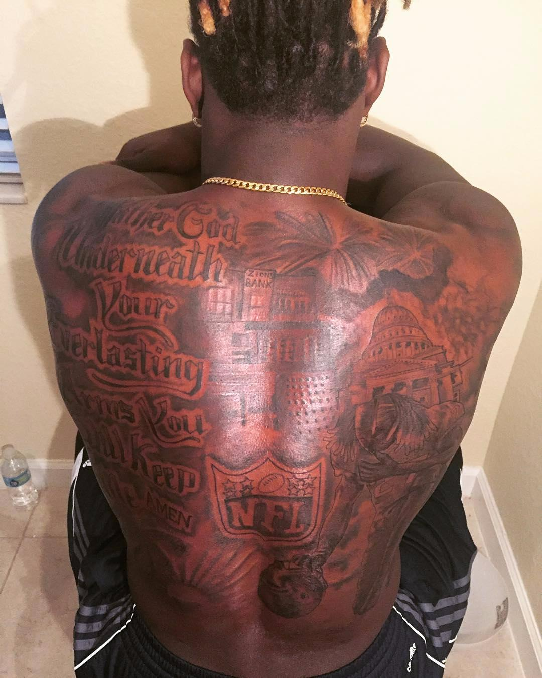 """The gridiron star has a huge back tattoo with the words: """"Father God underneath your everlasting arms you will keep me, Amen."""""""
