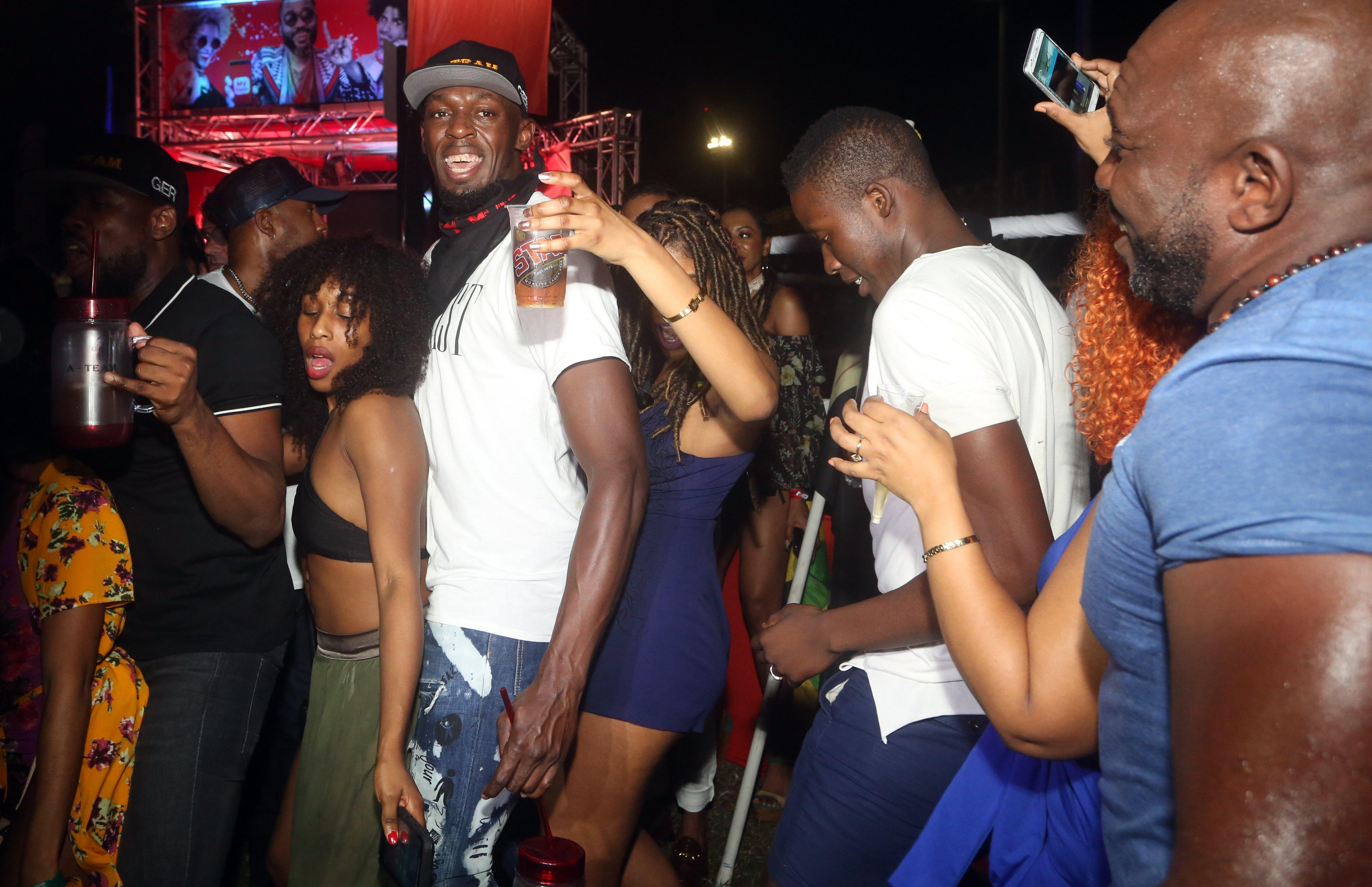 Usain Bolt was all smiles as he danced between two women