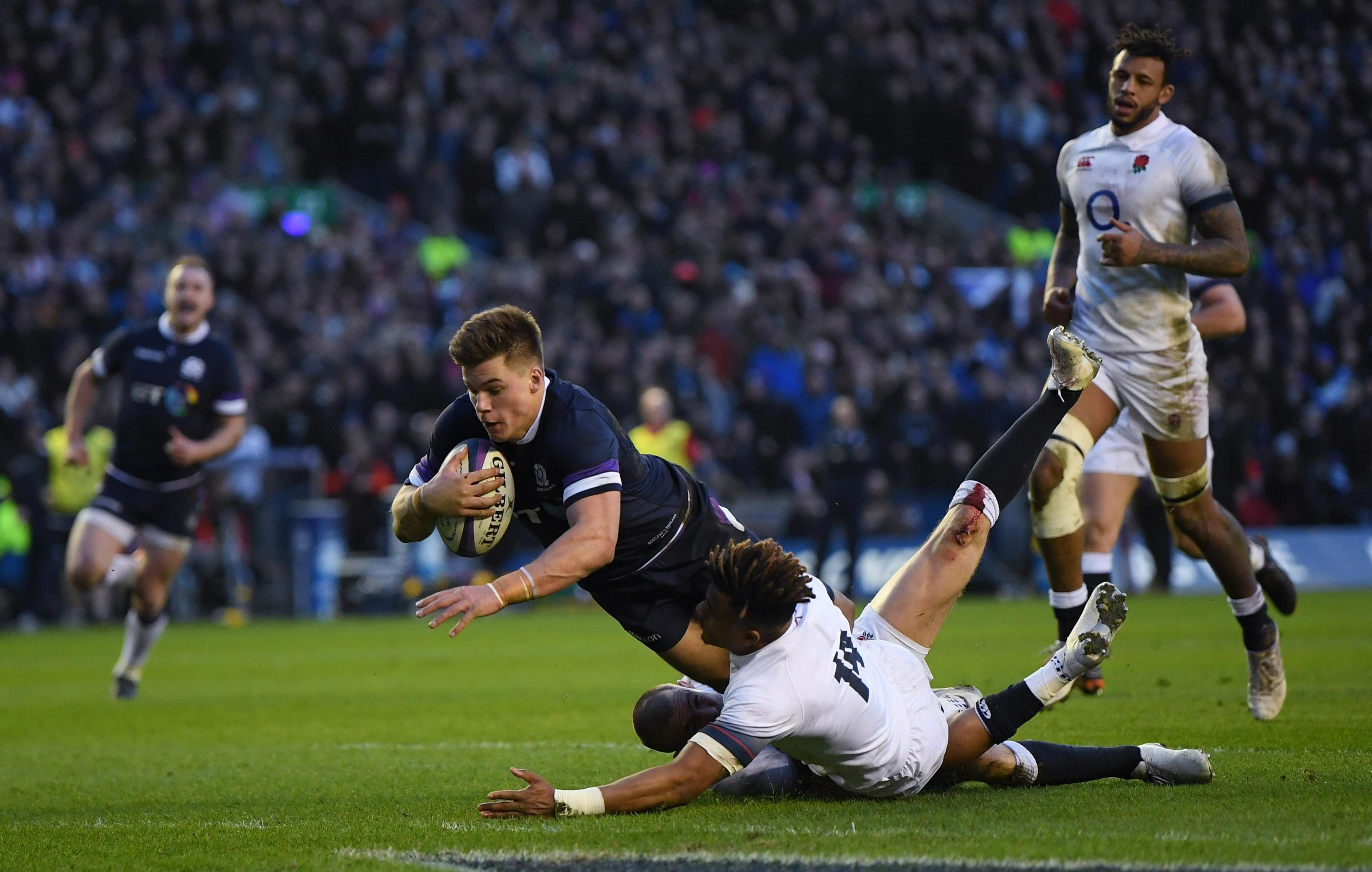 Huw Jones scores Scotlands third try despite the best efforts of Englands Anthony Watson
