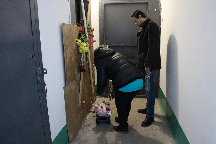 Neighbours leave tributes next to the now boarded up faulty lift