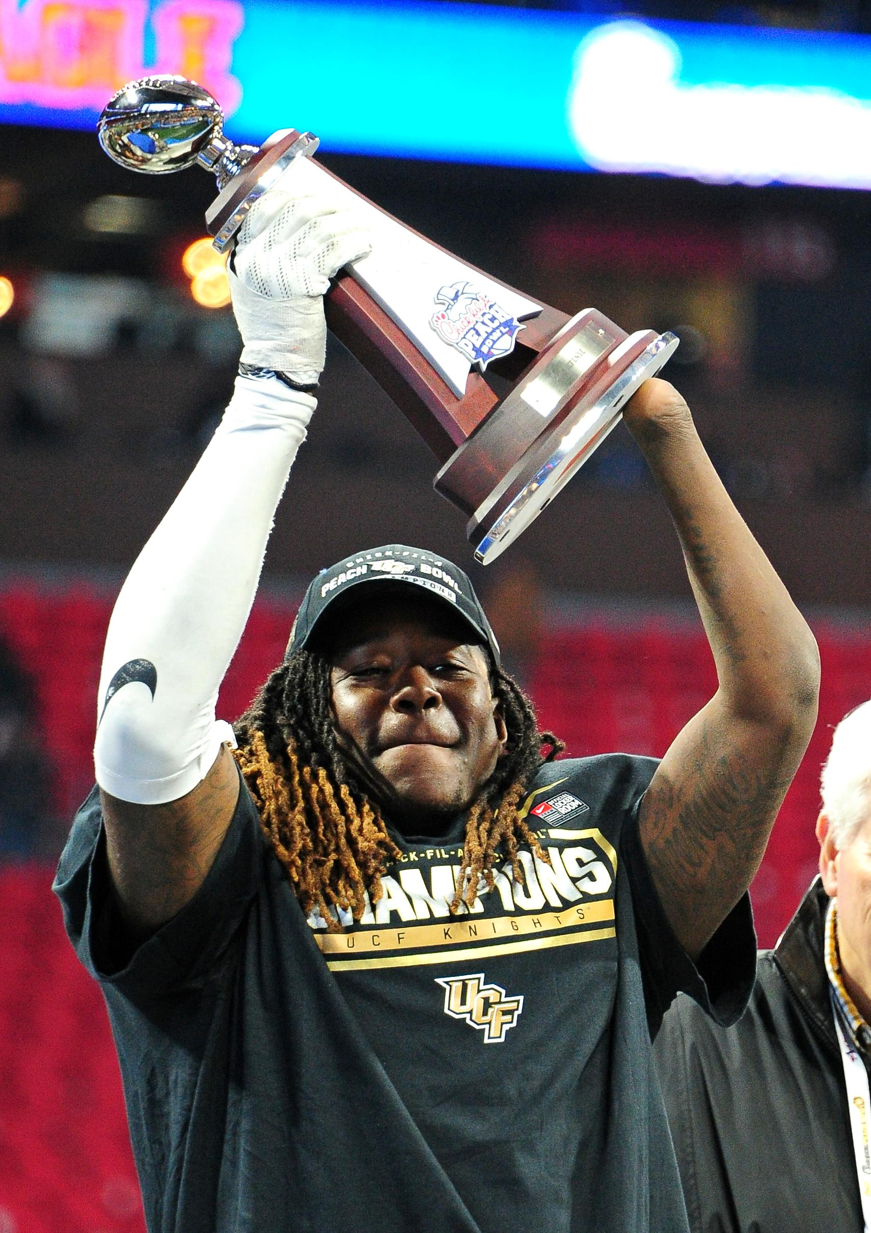 Shaquem lifts the trophy at the Peach Bowl in January during his final collegiate game with University of Central Florida