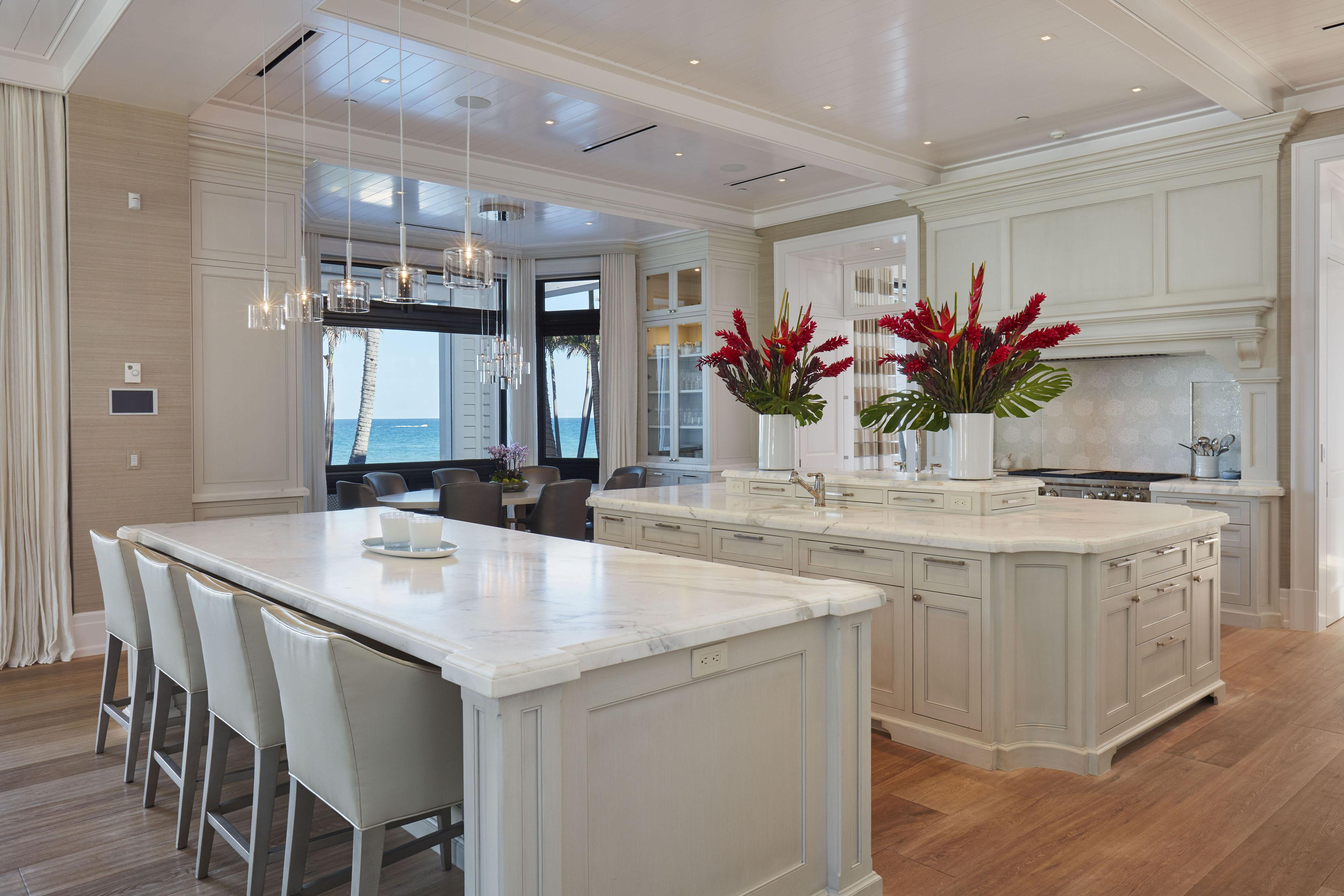 Beautiful kitchen includes a number of tables to eat at and stunning counters