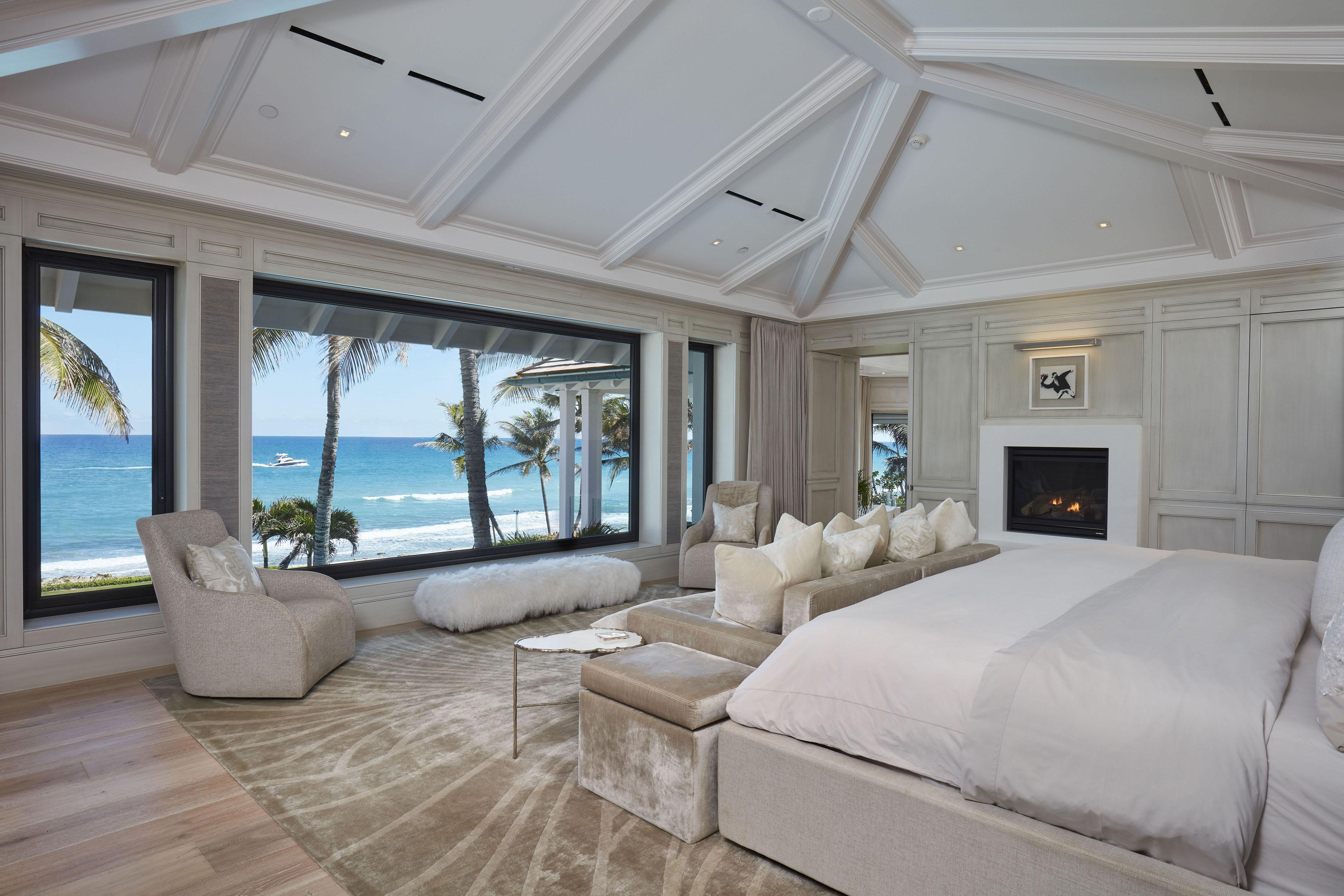 Stunning master bedroom has a view of the ocean and a built-in fireplace