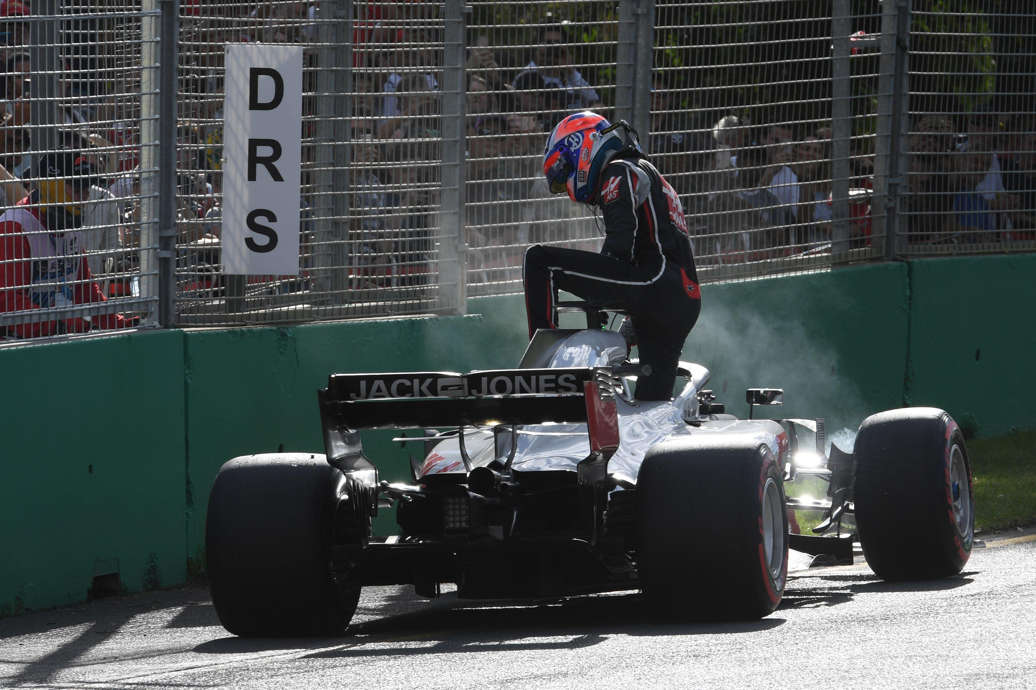 Romain Grosjean leaves his car after crashing in Melbourne