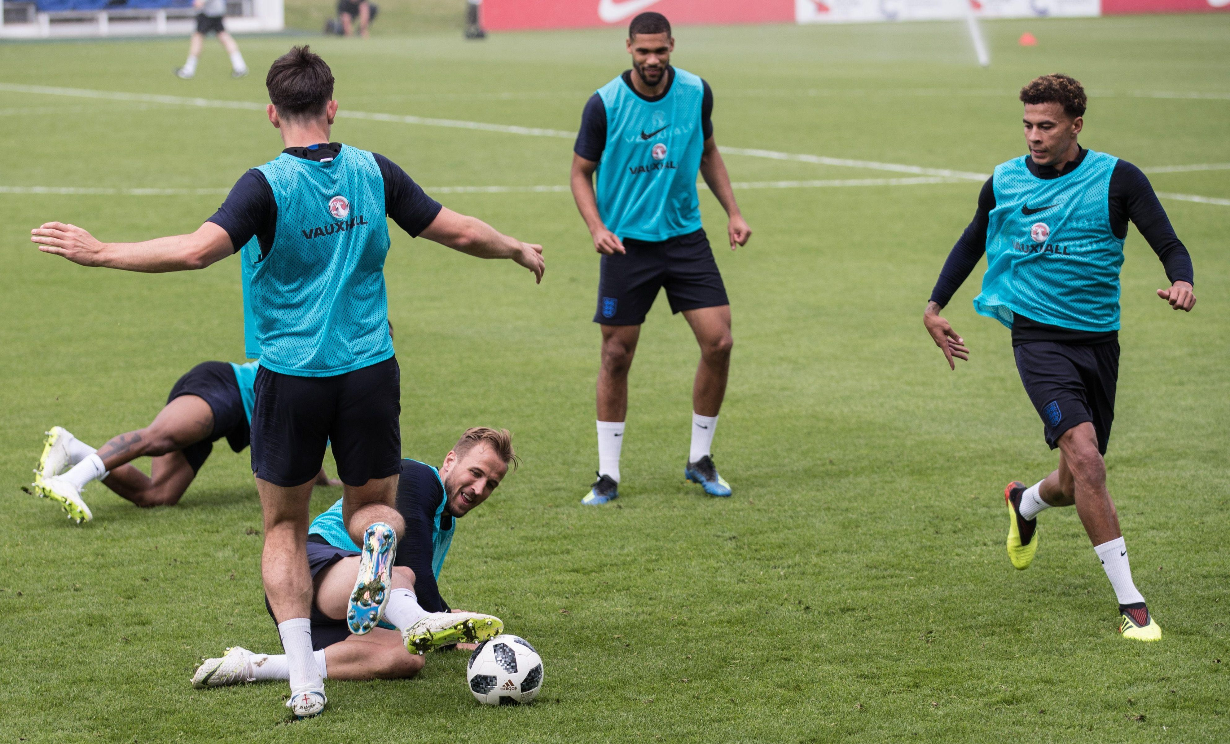 Harry Kane lunges in to tackle Harry Maguire during the training session