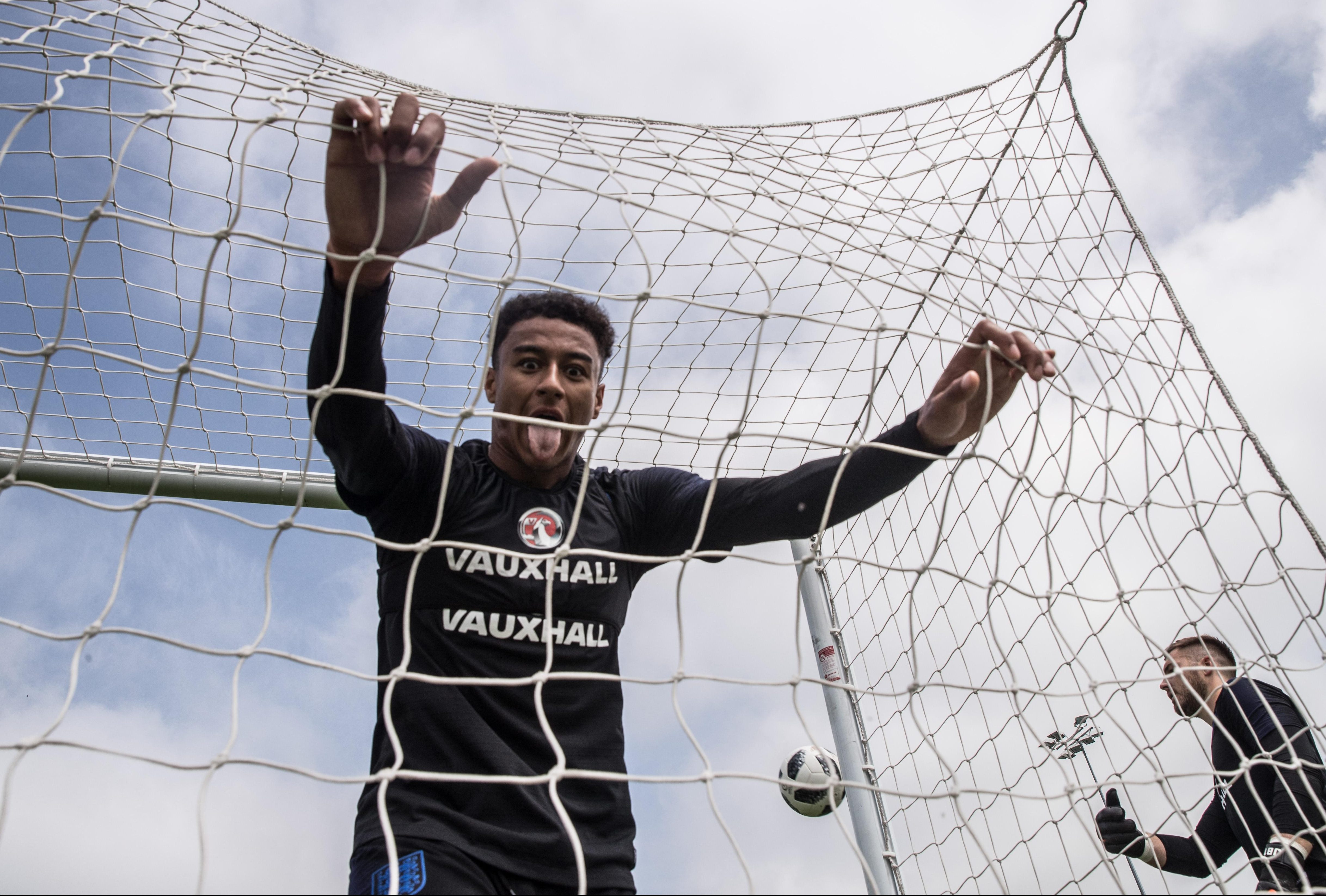 Jesse Lingard falls into the net after missing a chance to score during training