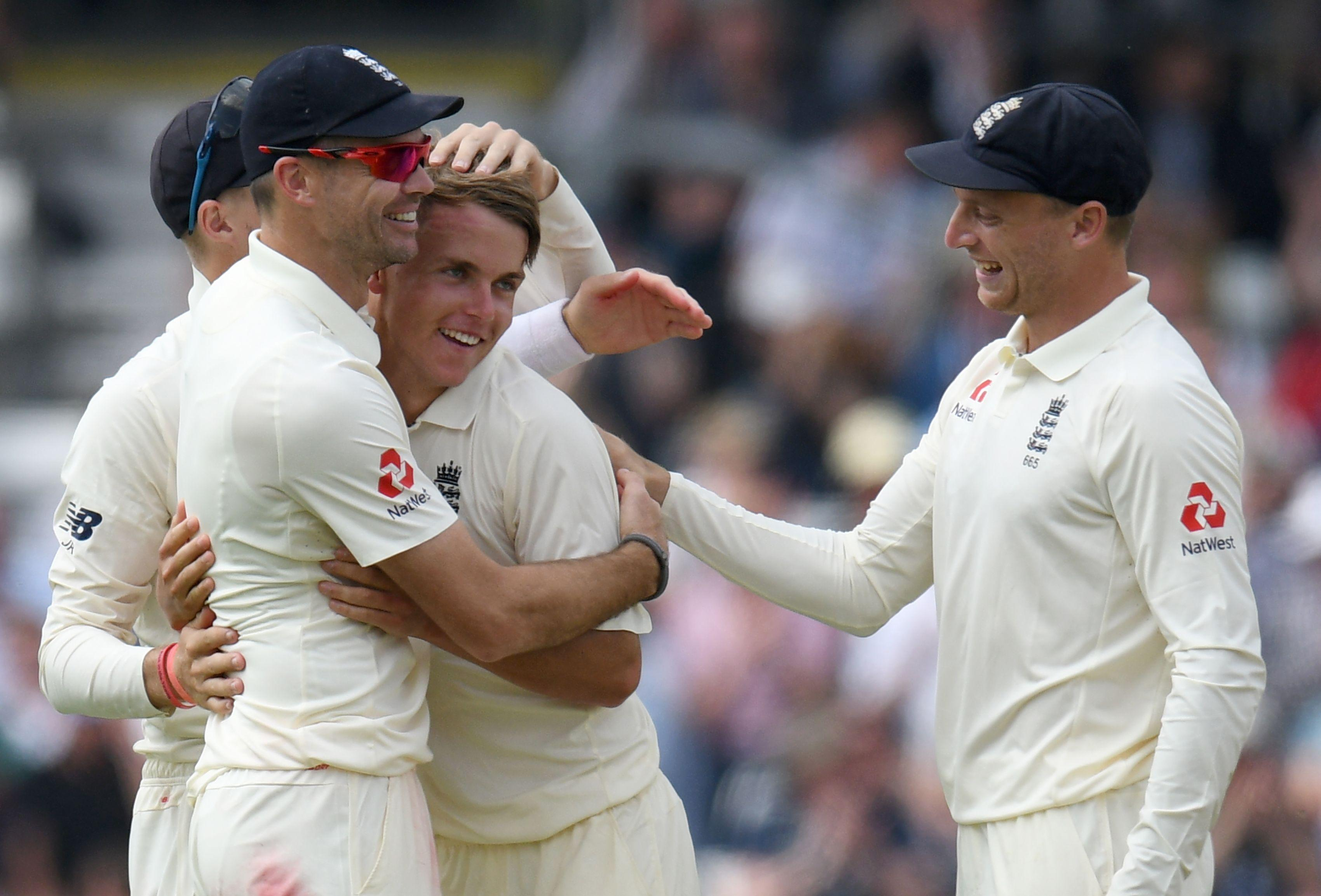 Sam Curran is congratulated by James Anderson and Joe Root after taking the wicket of Shadab Khan
