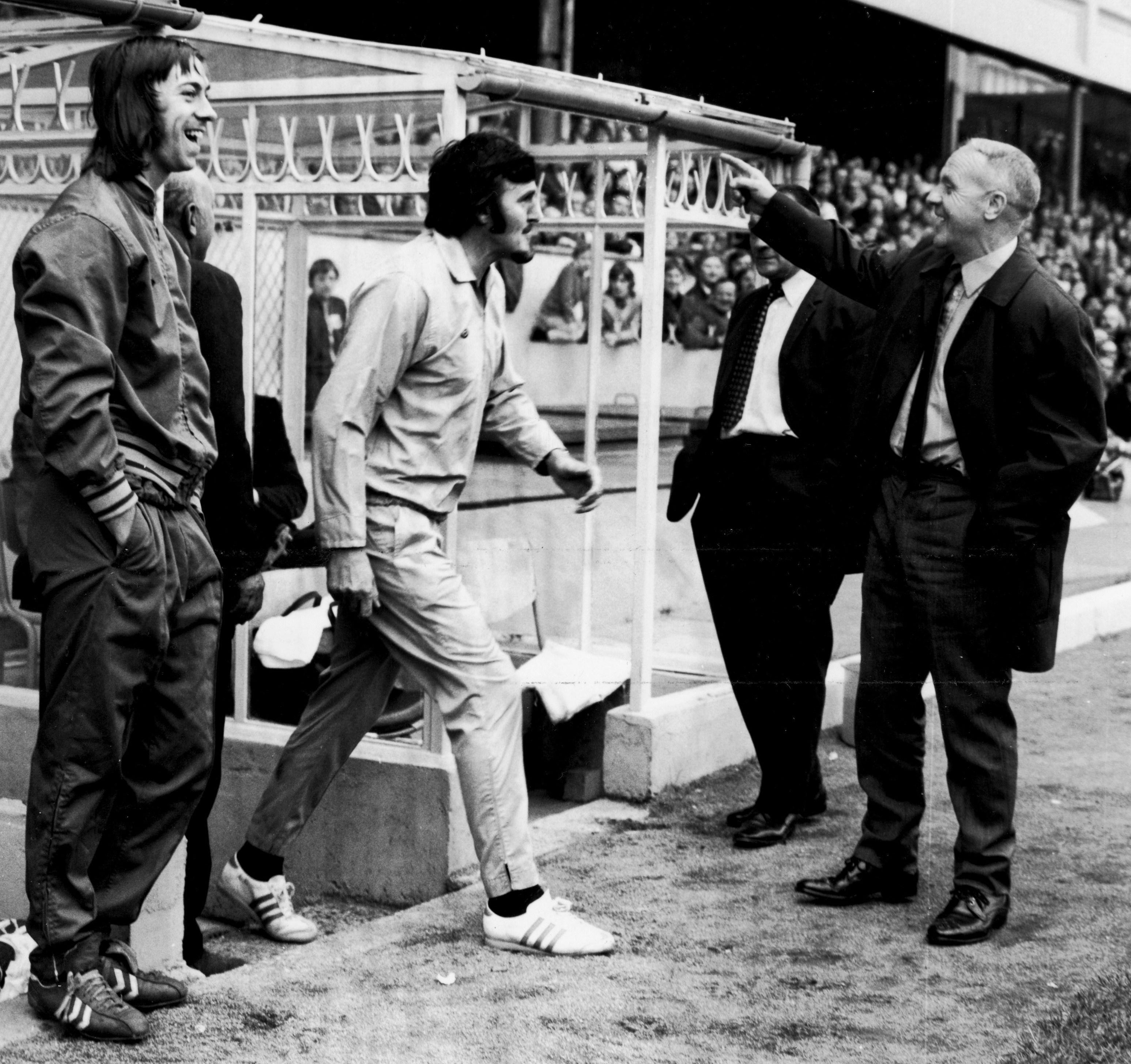 Arsenal's Charlie George Shankly share a laugh as commentator Jimmy Hill emerges in a sky blue tracksuit to take over from a linesman who had limped off injured