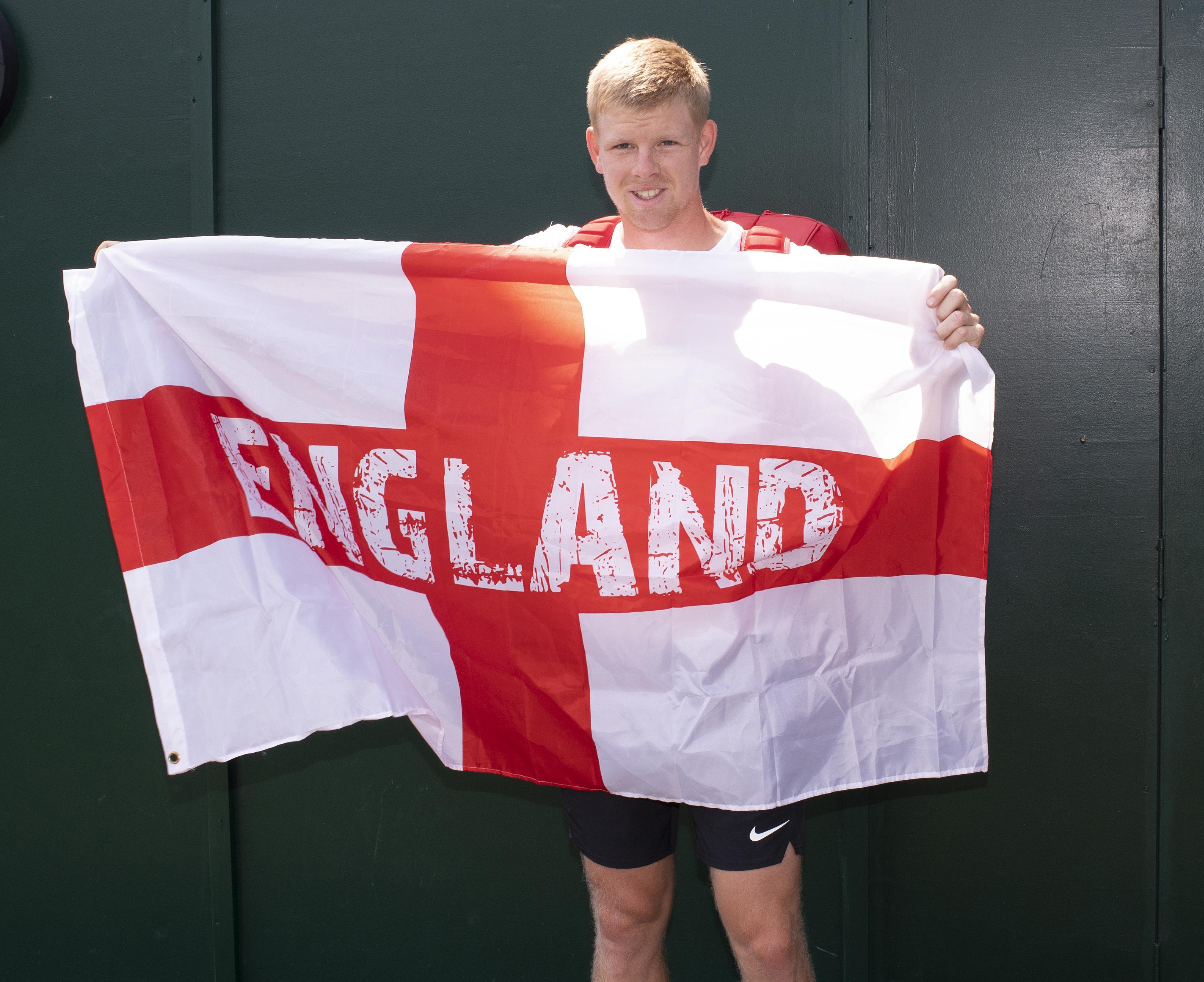 British No1 Kyle Edmund poses proudly with his England flag as he prepares to play Djokovic