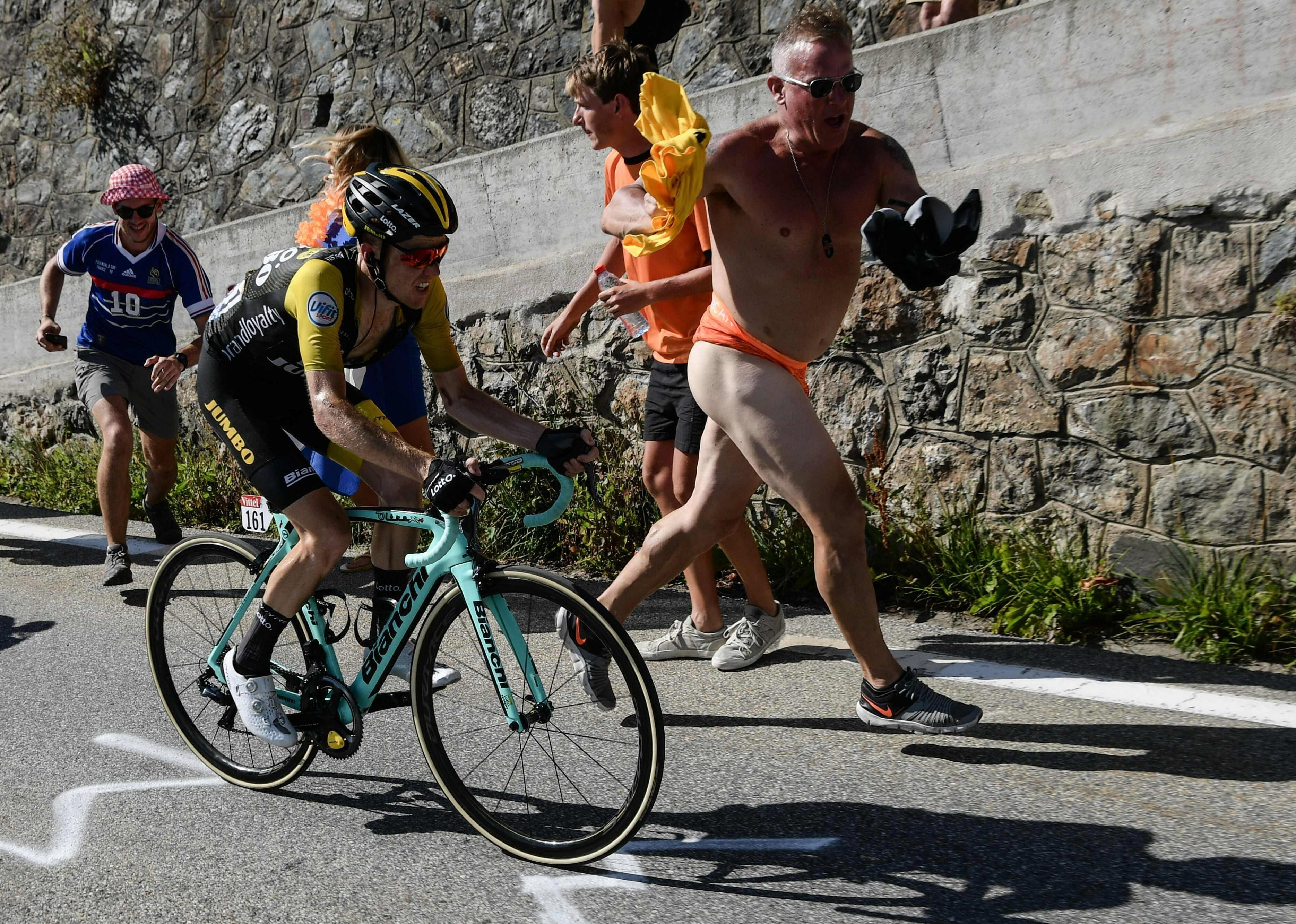 Spectators run next to Holland's Steven Kruijswijk in the ascent to l'Alpe d'Huez on the twelfth stage on Thursday