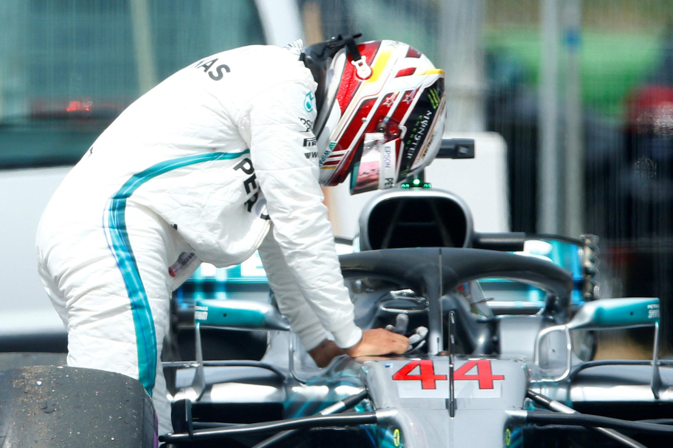 Hamilton contemplates his misfortune as he leaves his car on the side of the track