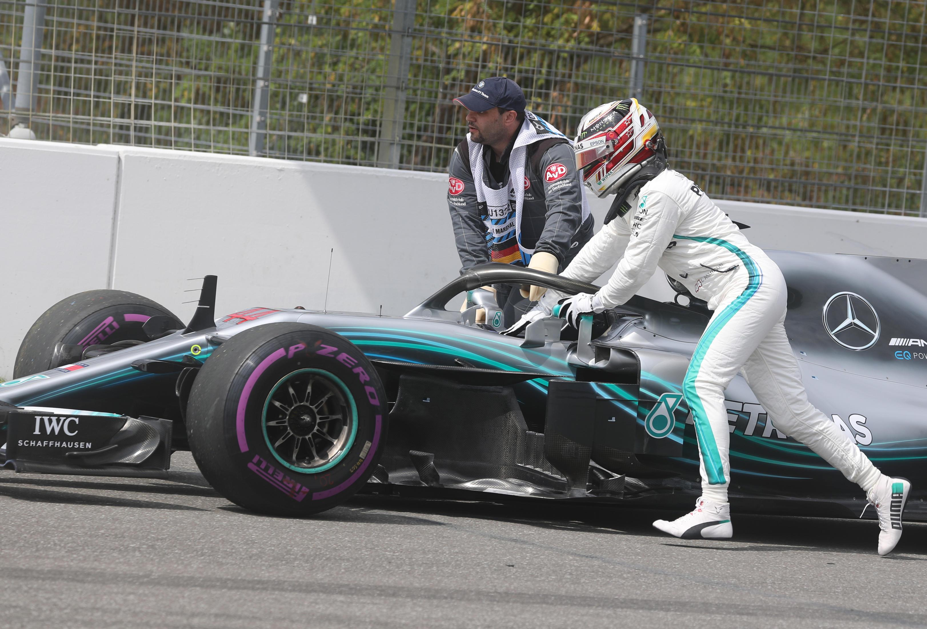 Lewis Hamilton cut a dejected figure as he struggled to push car back to pits