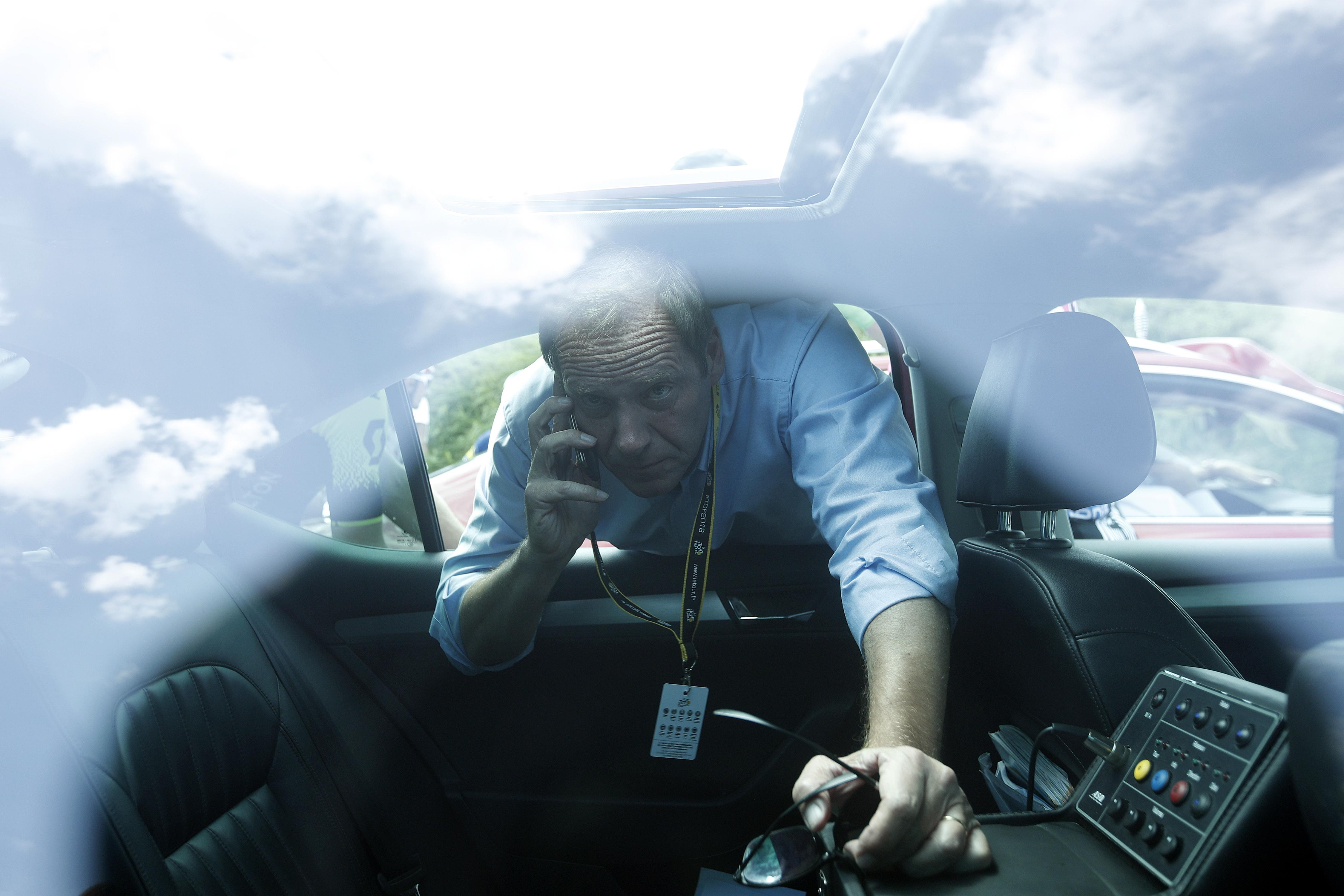 Race director Christian Prudhomme gets on the phone to local law enforcement over the delay