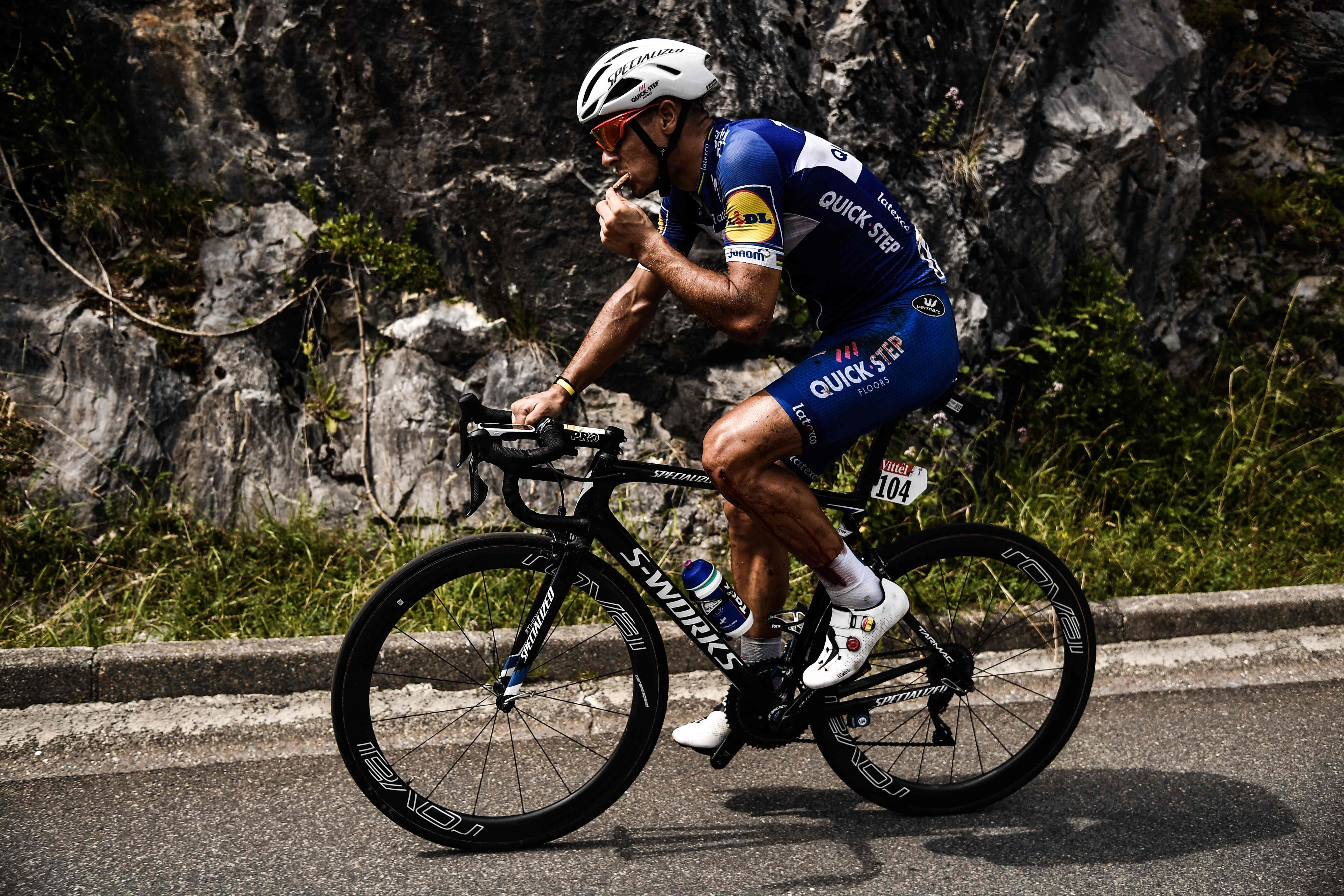 Philippe Gilbert tucks into a snack after he managed to carry on racing despite his fall