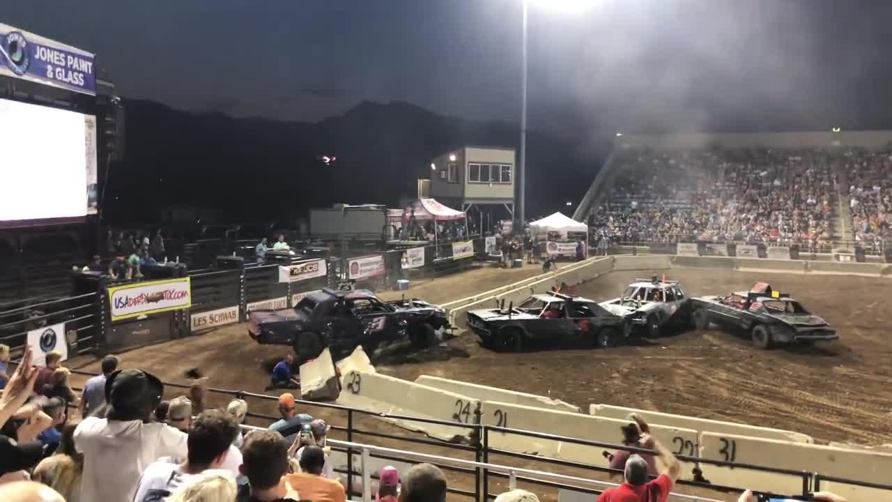A demolition derby worker has his legs crushed by a concrete barricade