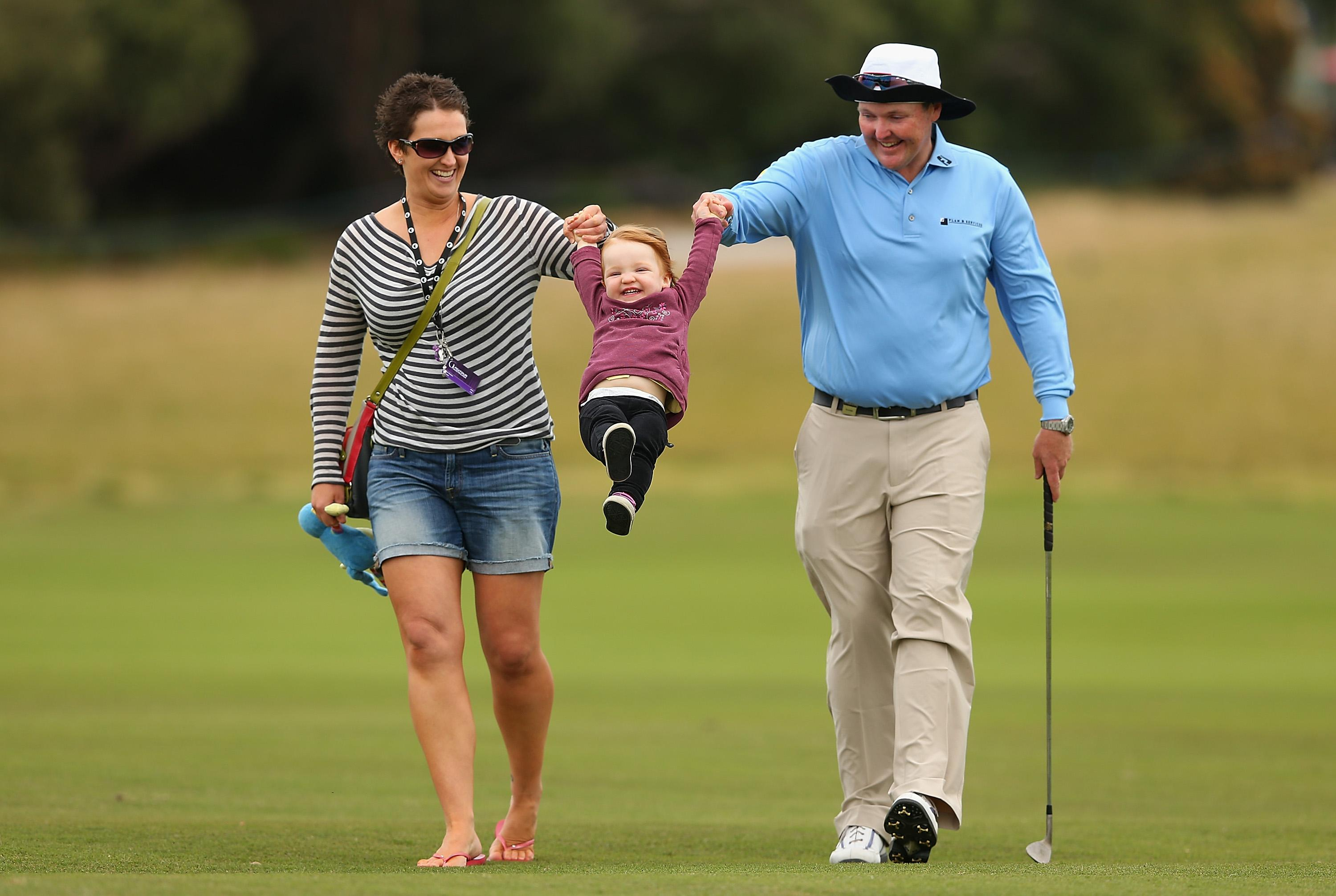 Jarrod Lyle of Australia walks the course with wife Briony and daughter Lusi ahead of the 2013 Australian Masters