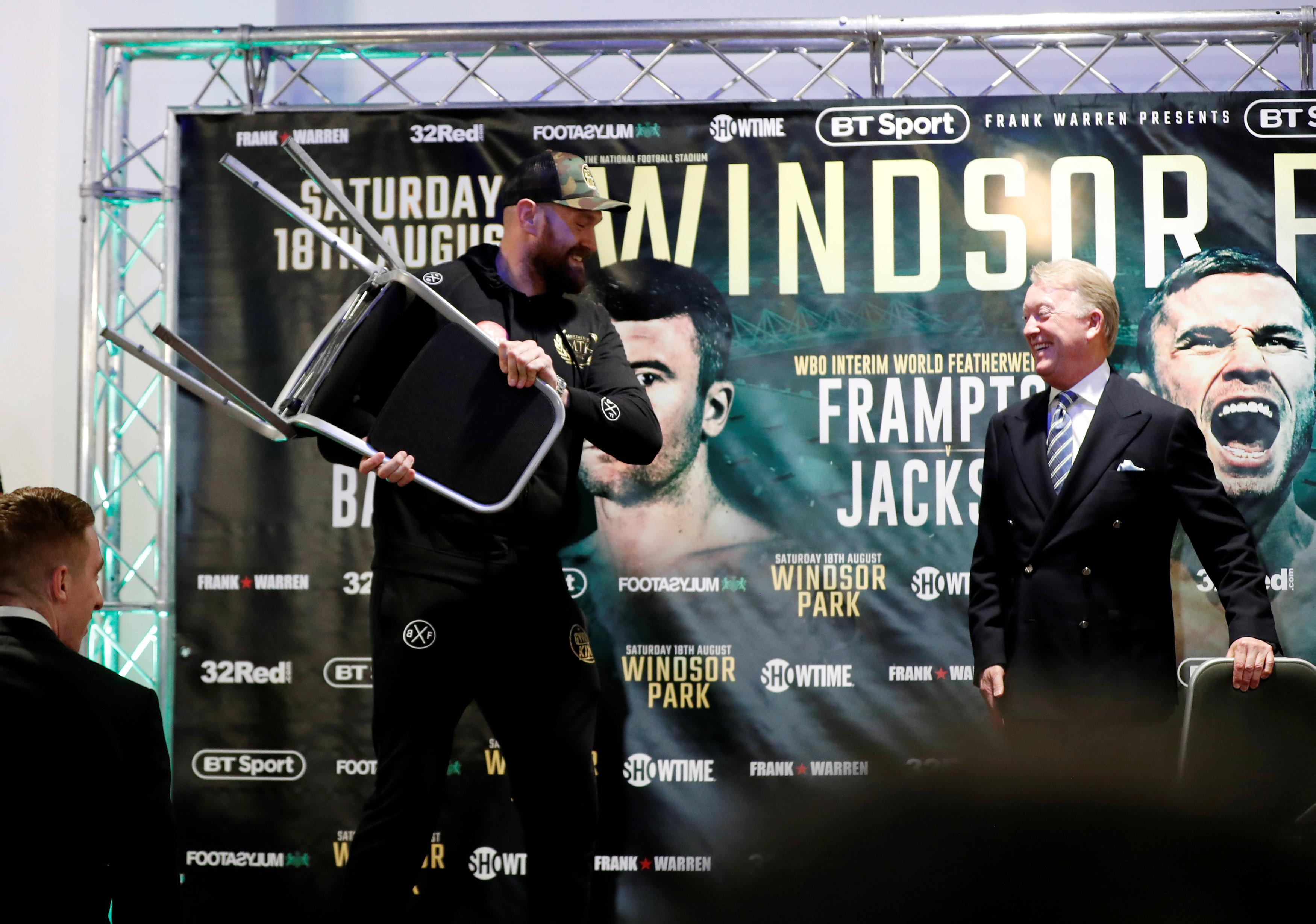 Tyson Fury picks up a chair during his press conference