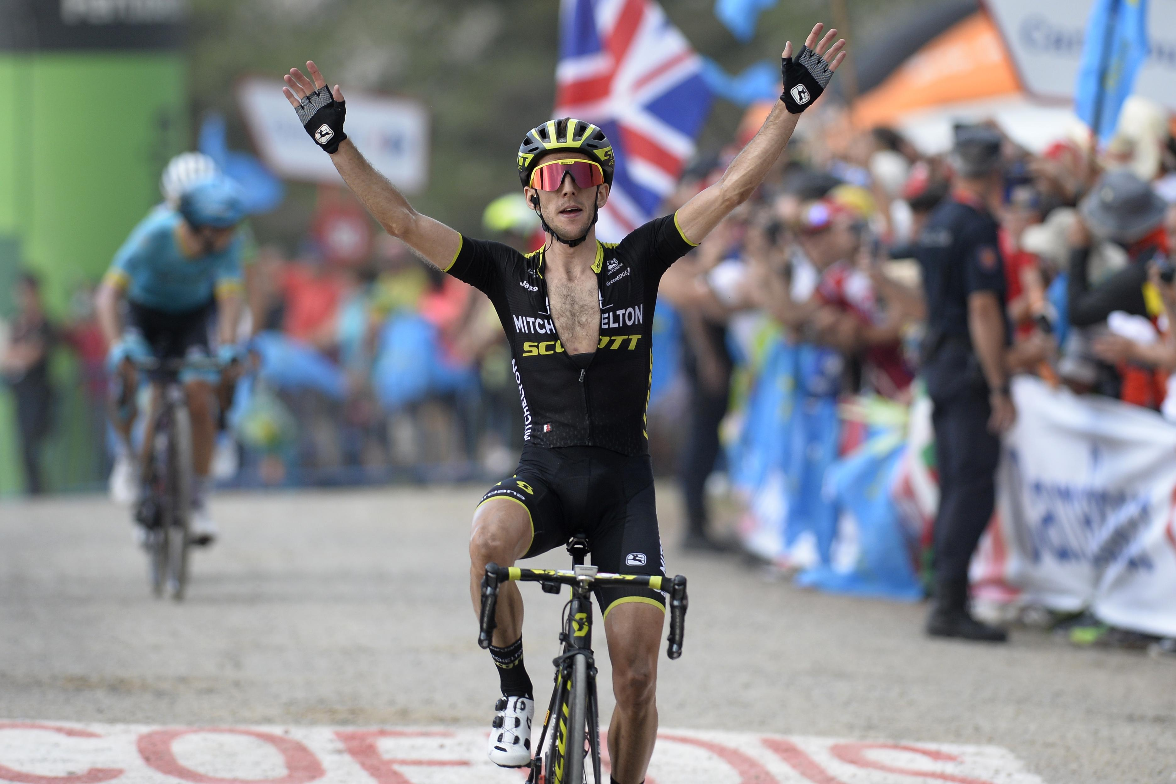 Simon Yates holds his arms aloft after winning stage 14 of the Vuelta a Espana