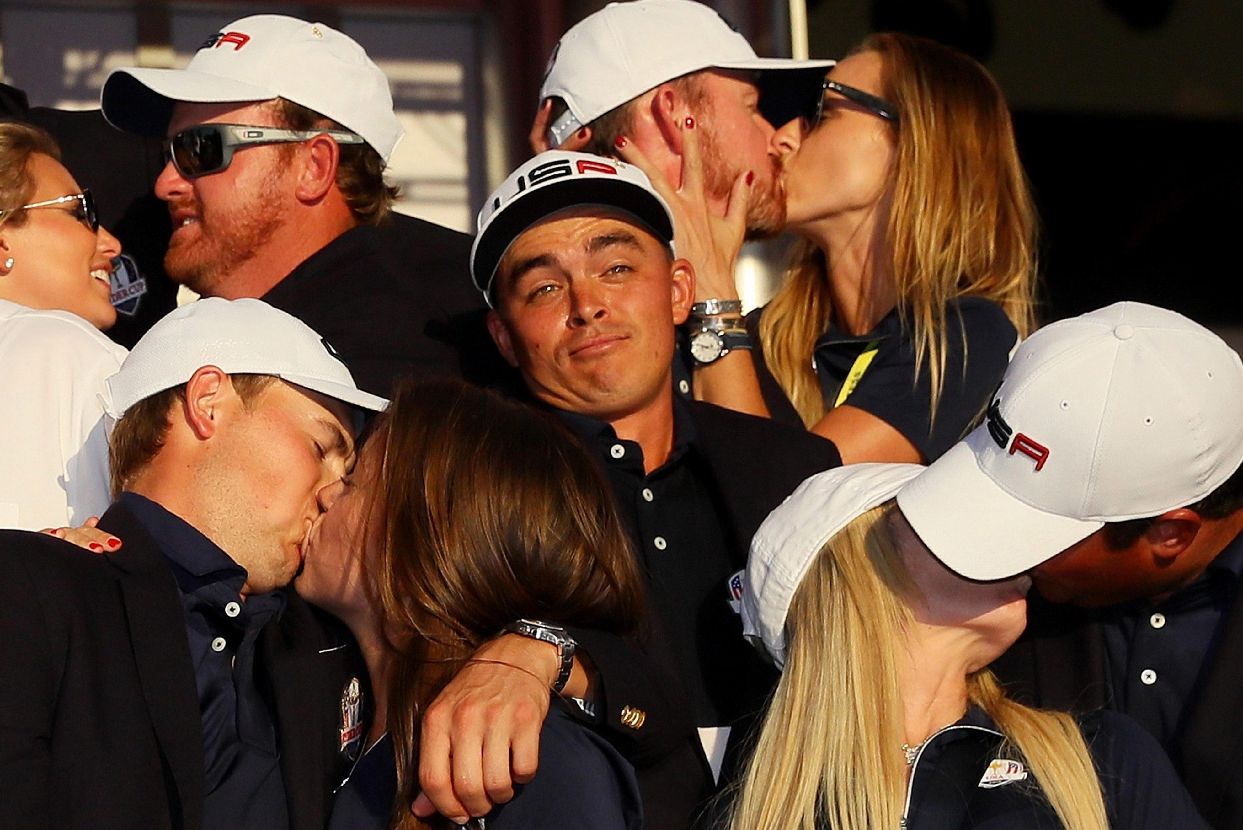 US ace Rickie Fowler looks on as J.B. Holmes, Erica Holmes, Jimmy Walker, Erin Walker, Jordan Spieth, Annie Verret, Justine Reed and Patrick Reed celebrate during the 2016 singles matches at Hazeltine