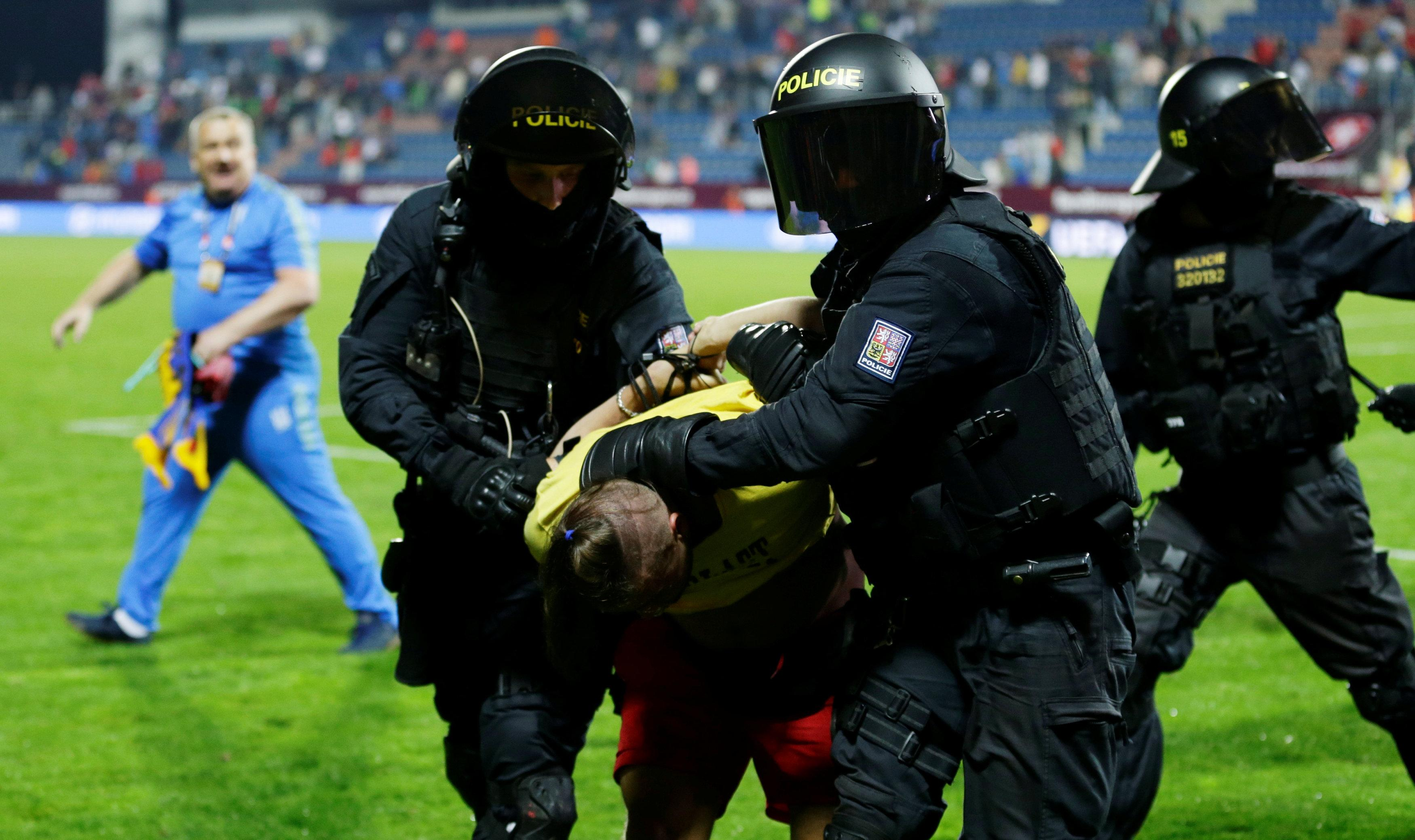 Riot police intervened after Thursday night's game as they escorted pitch invaders off the field