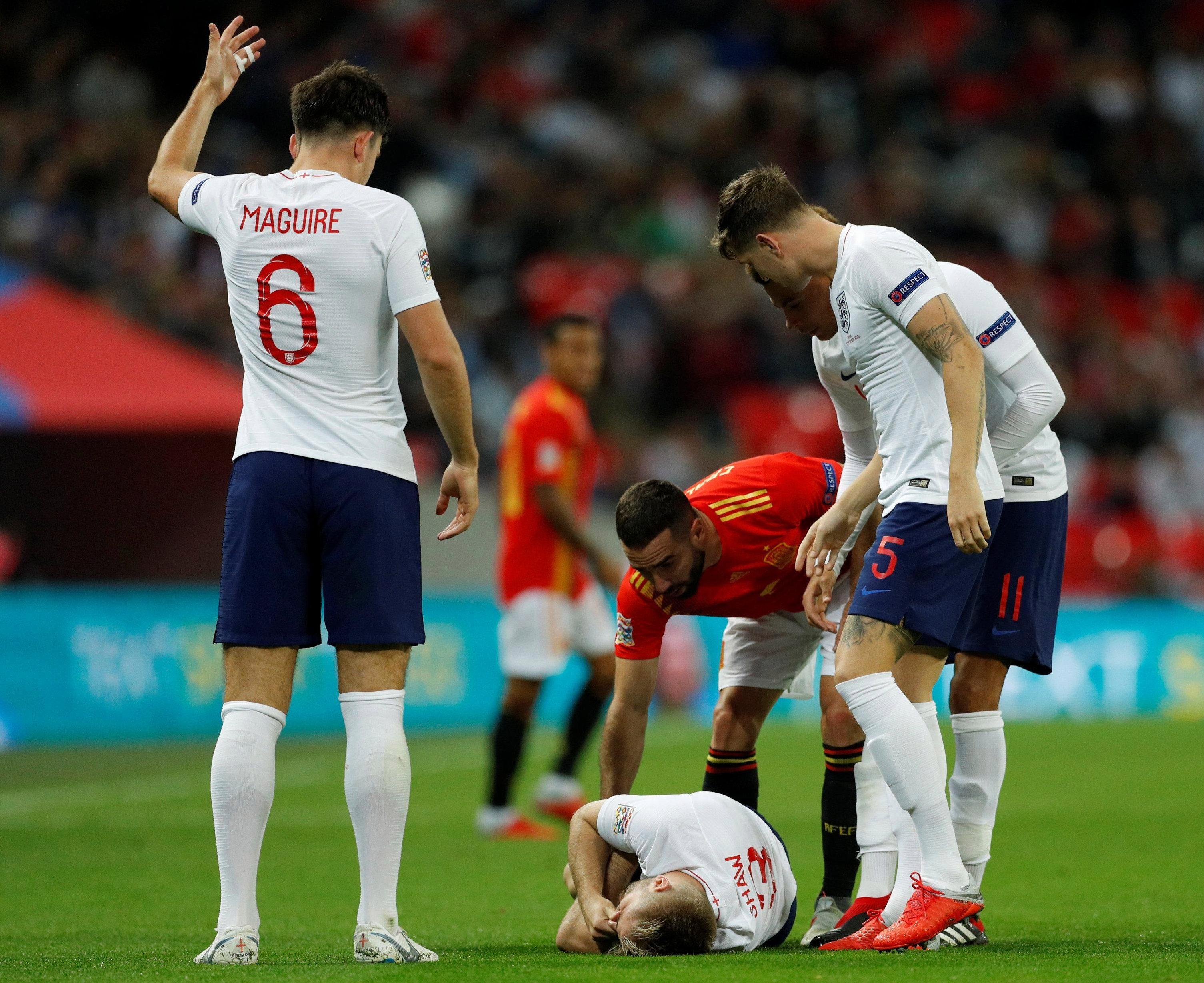 England stars Harry Maguire, John Stones and Dele Alli, plus Spain's Dani Carvajal, look on as Luke Shaw reels