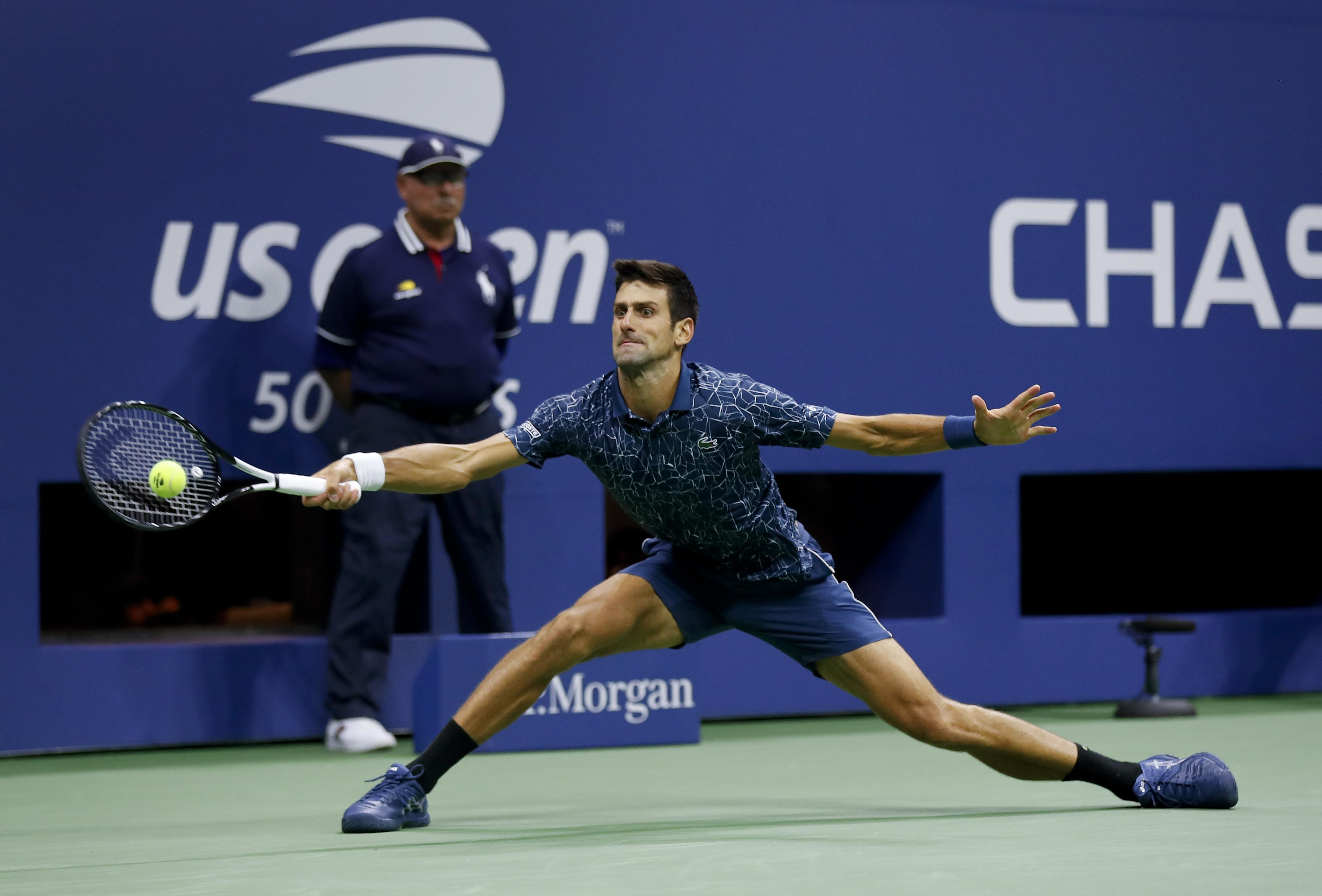 Novak Djokovic returns a shot at full stretch against Juan Martin del Potro